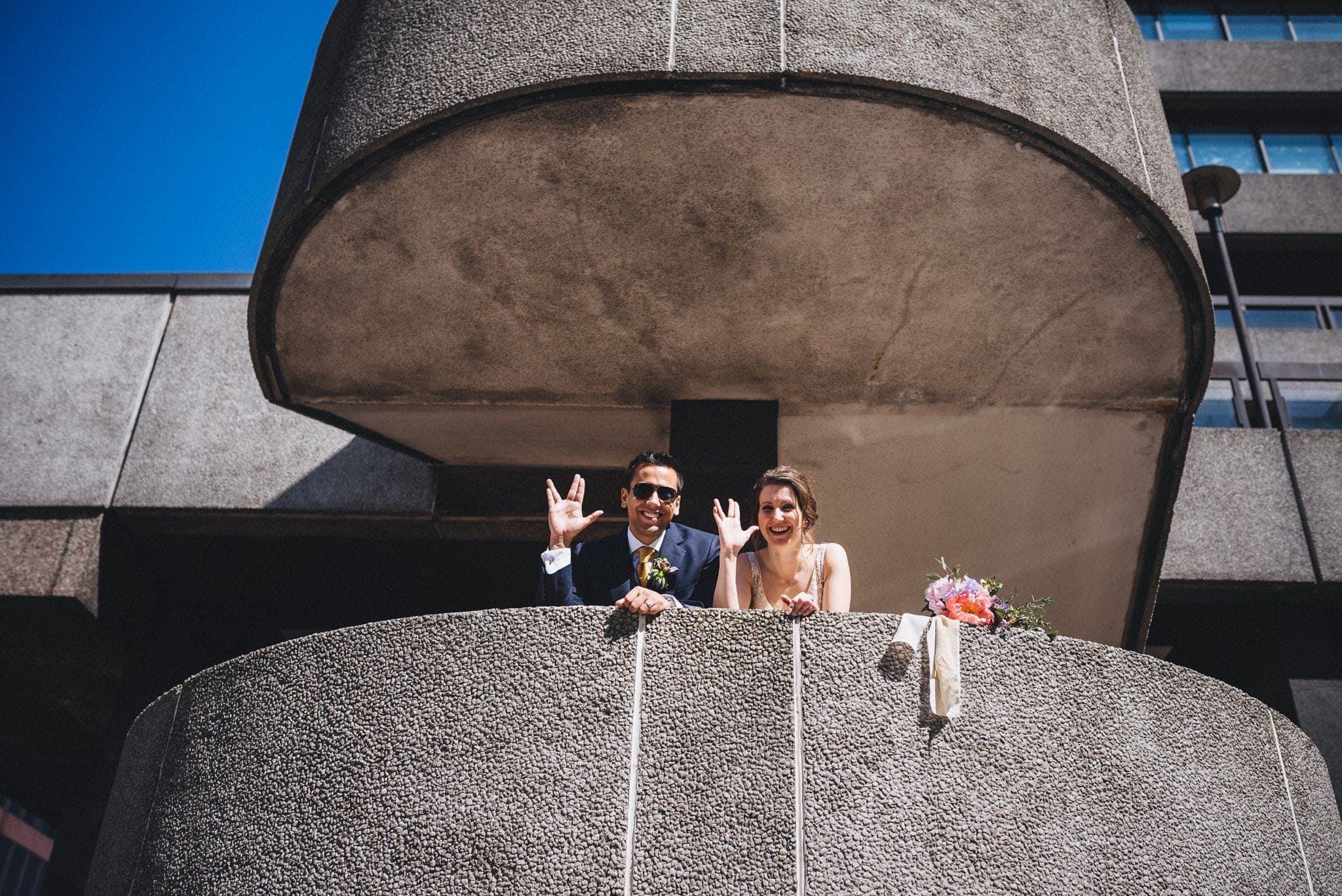 Bride and groom make Live Long and Prosper signs in concrete stairwell