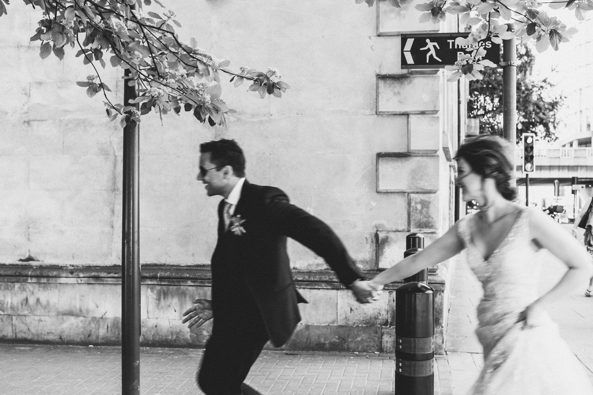 Bride and groom holding hand and running along London street