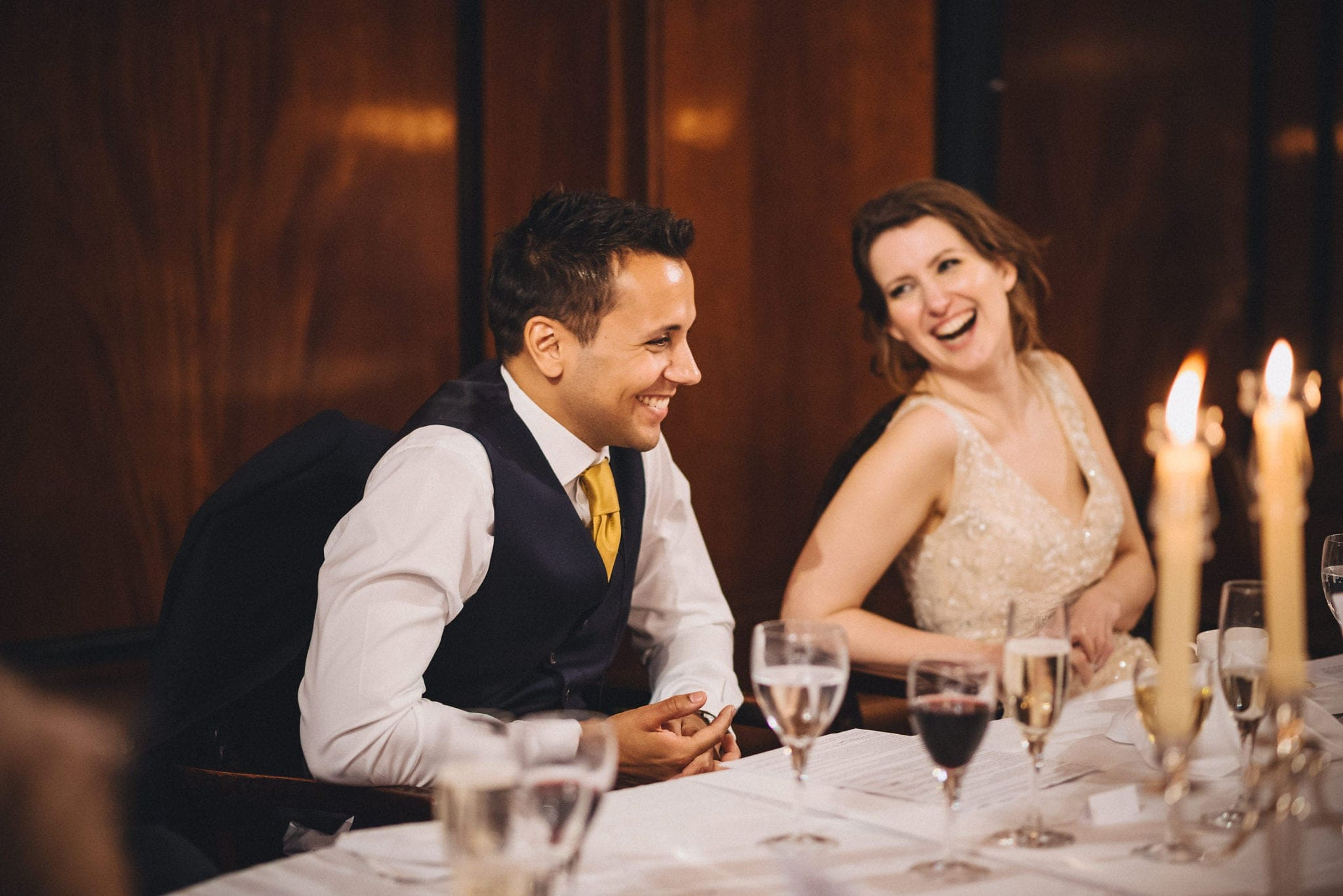 Bride and groom laugh at dinner table