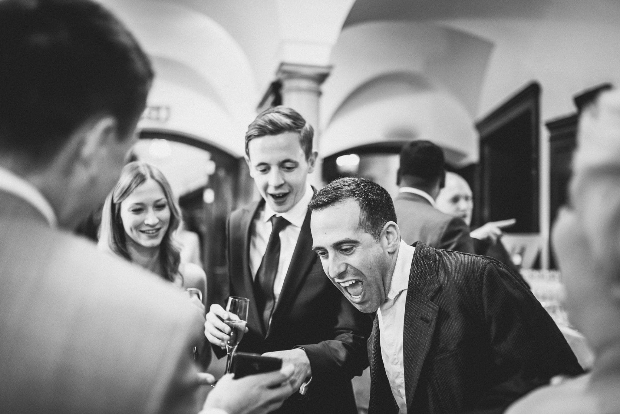 Black and white shot of guests laughing at something on an iPhone