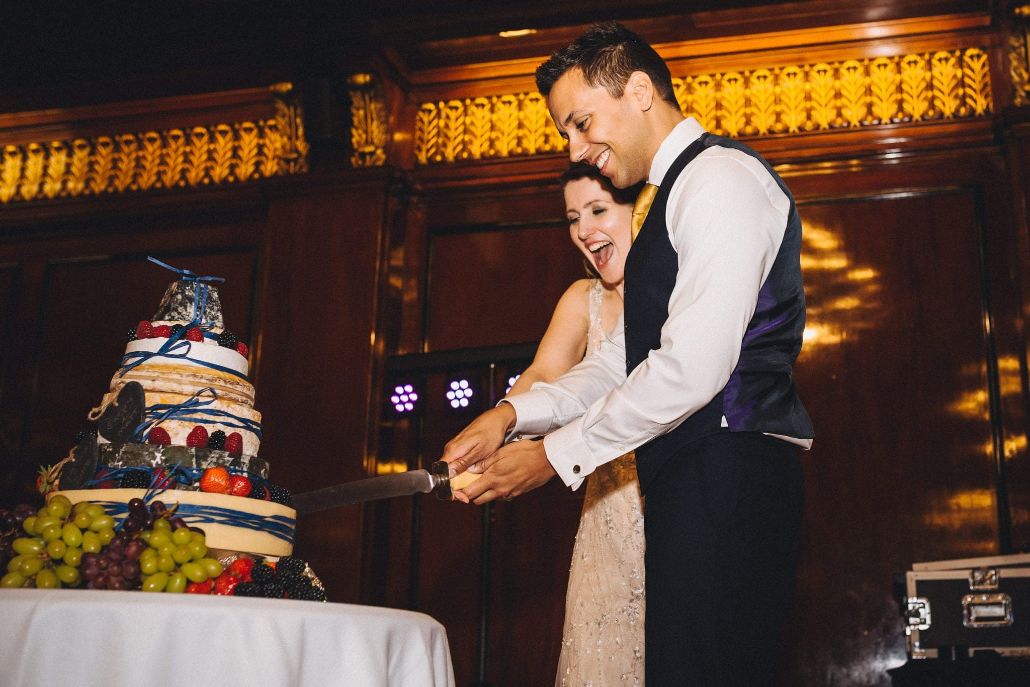 Bride and groom cut cheese wedding cake at relaxed London wedding