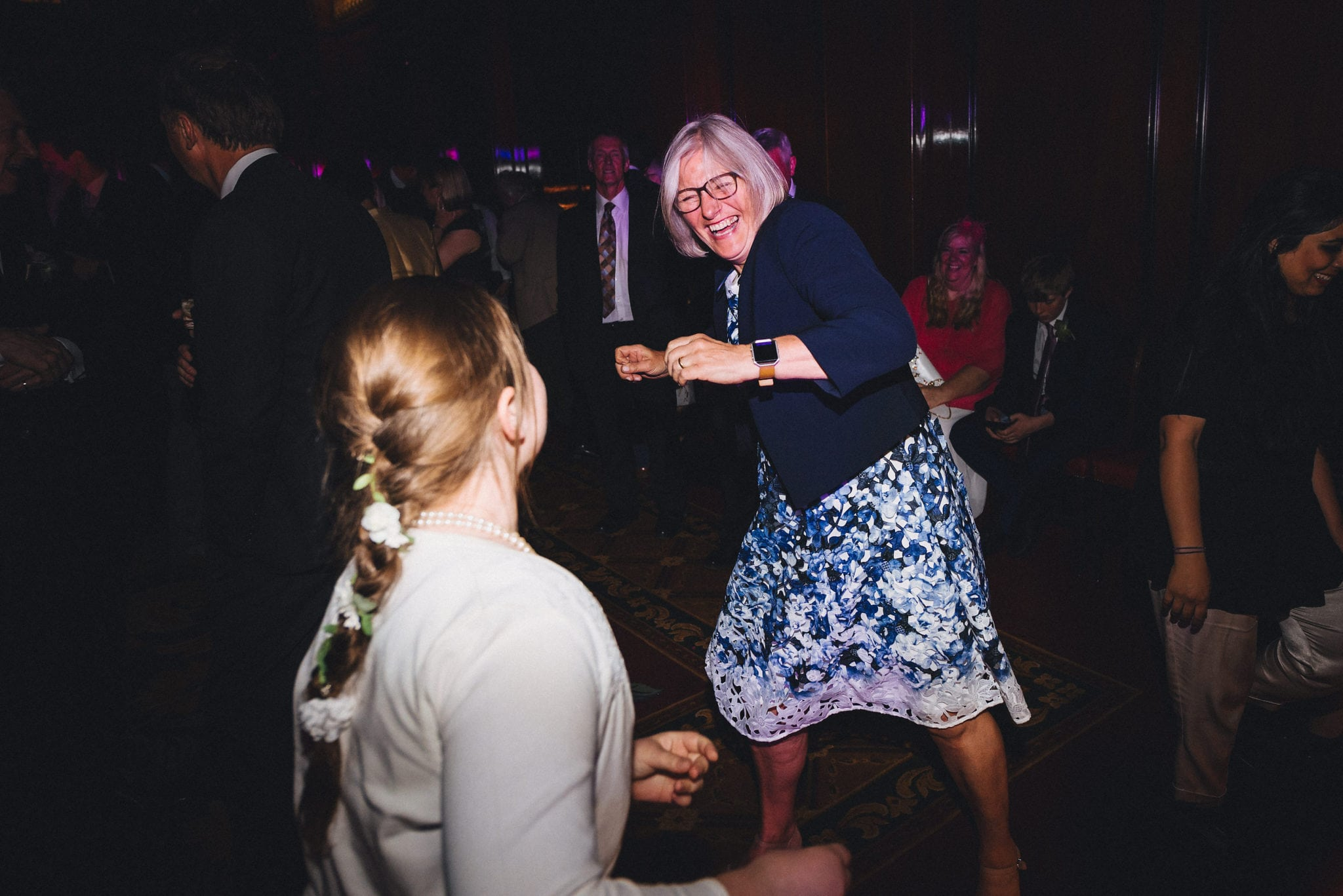 Woman dances with child at wedding reception