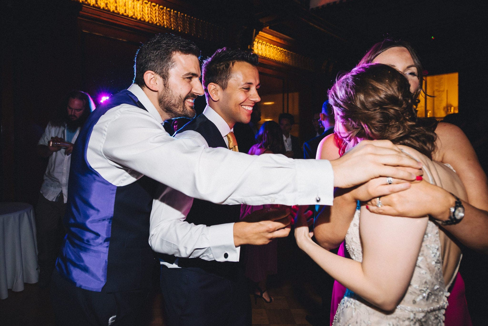 Guests hug bride and groom on dancefloor