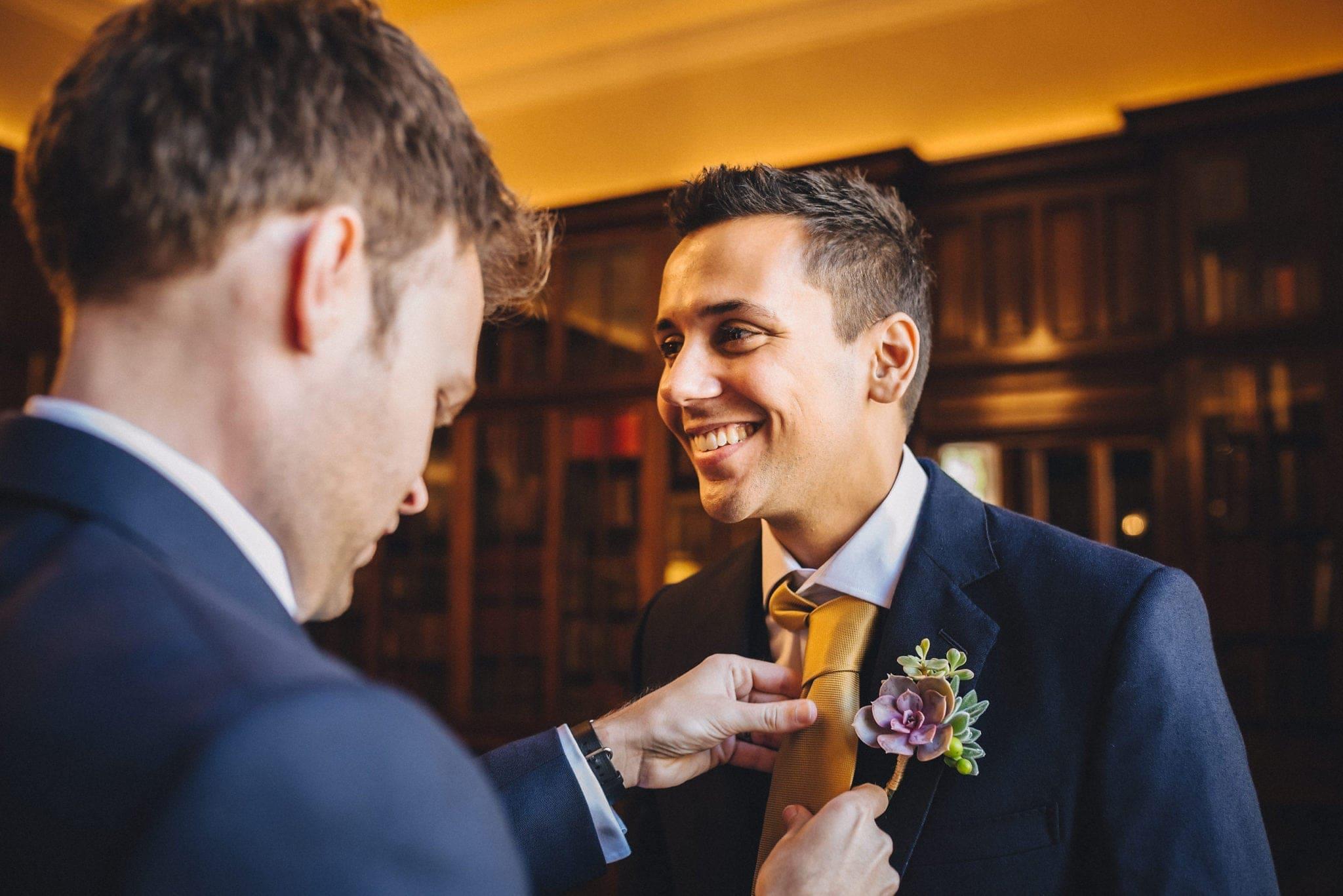 Groomsmen fastens groom's tie
