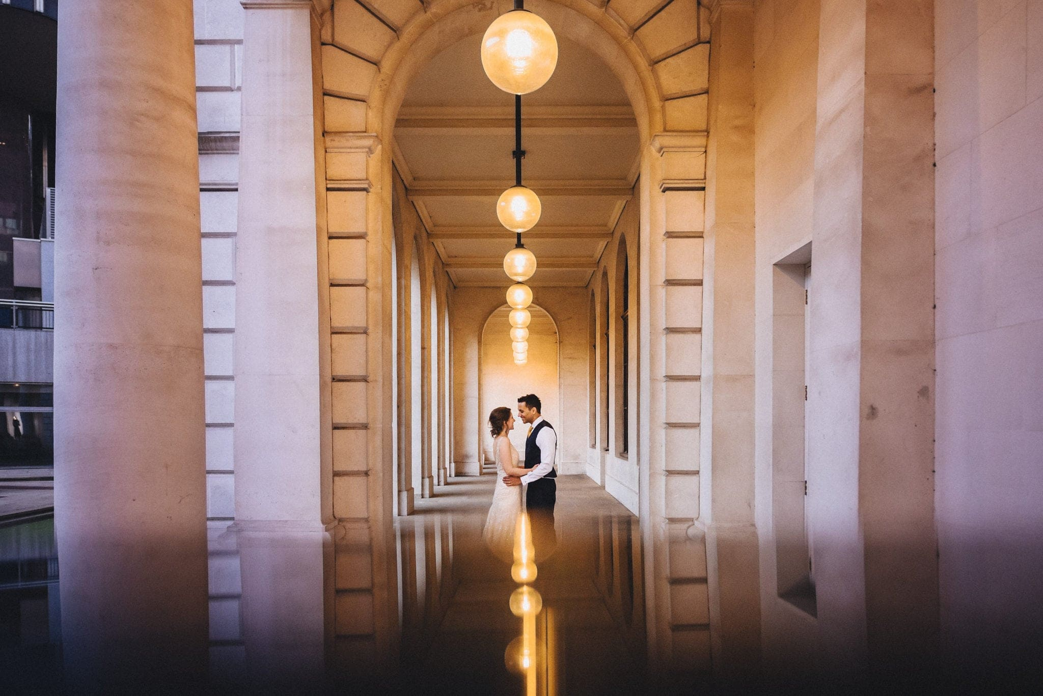 Bride and groom embrace in Merchant Taylor's Hall courtyard under the arches