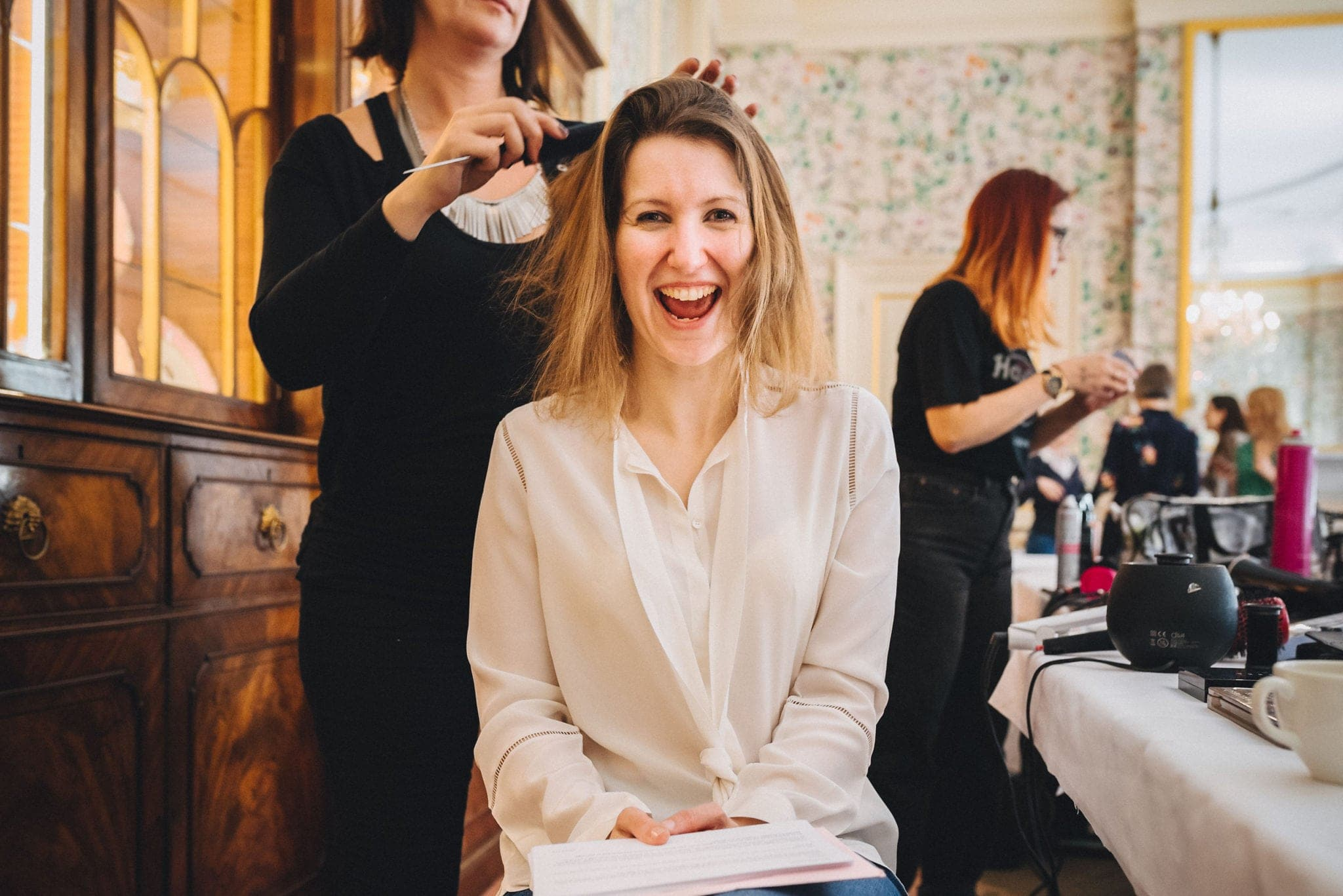 Bride laughs while having her hair done