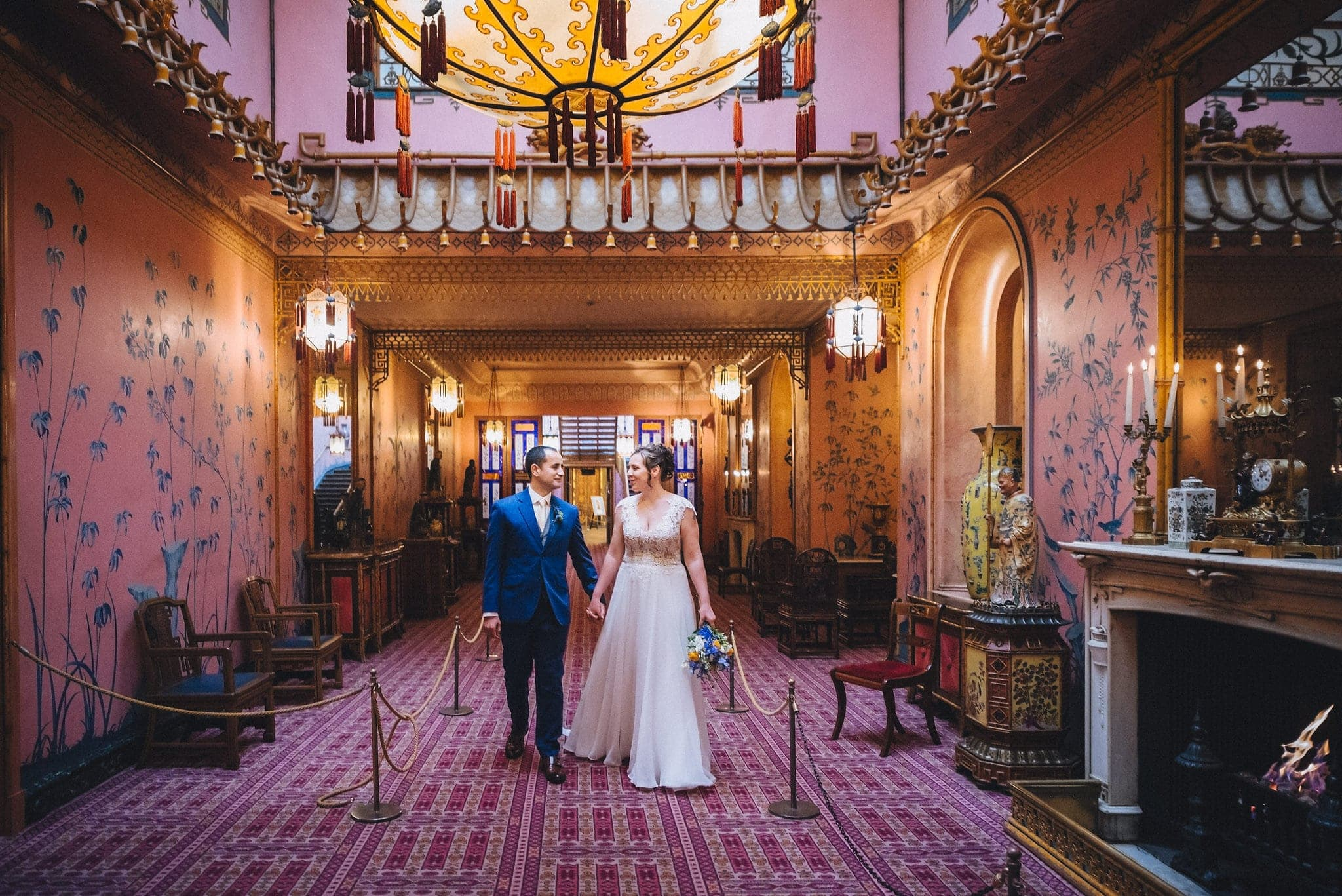 Bride and groom hold hands and walk through Brighton pavilion