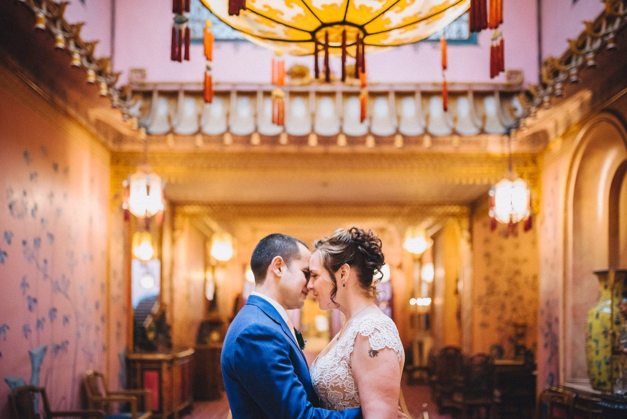 Bride and groom embrace in Brighton Royal Pavilion underneath lantern