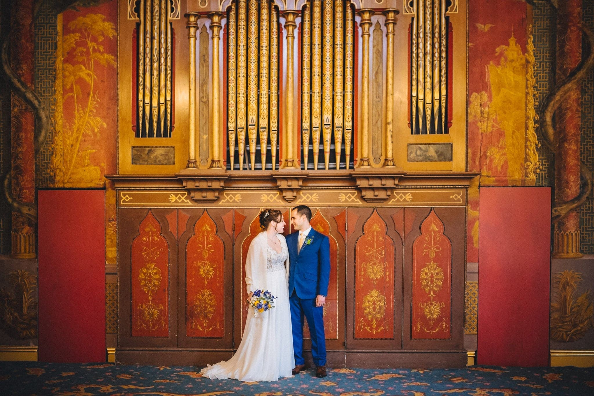 Bride and groom stand in front of red and gold organ in Brighton Royal Pavilion