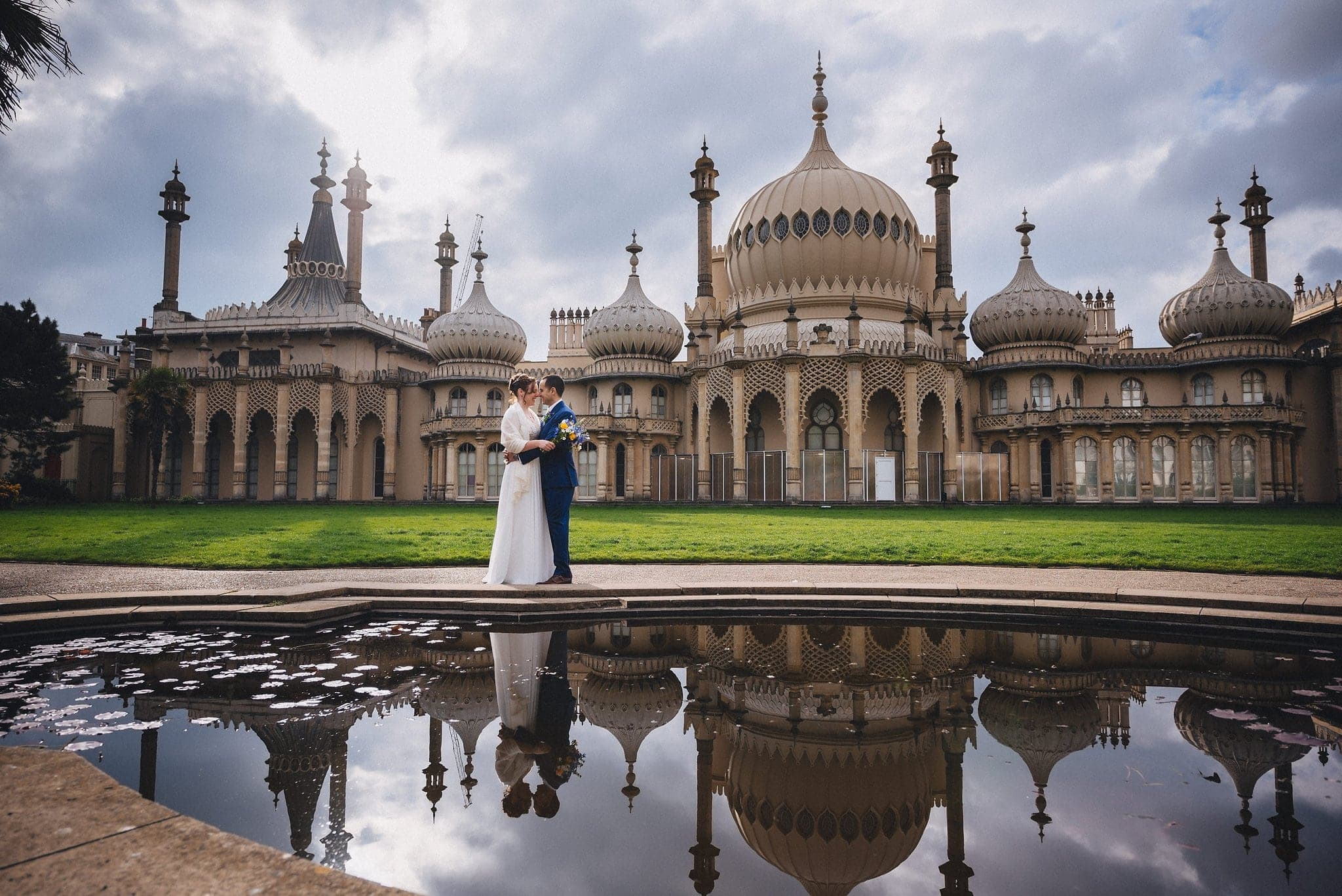 Bride and groom hugging in front of the Brighton Royal Pavilion with a reflection in the pond
