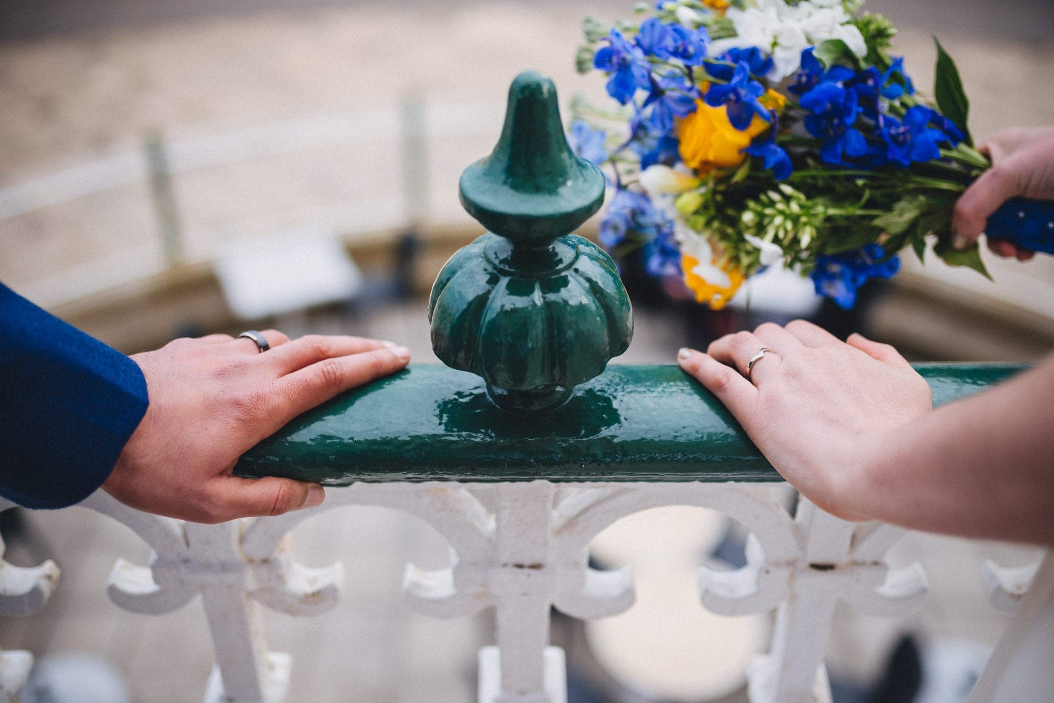 Close up of groom's and bride's hands on the railings of the Brighton bandstand