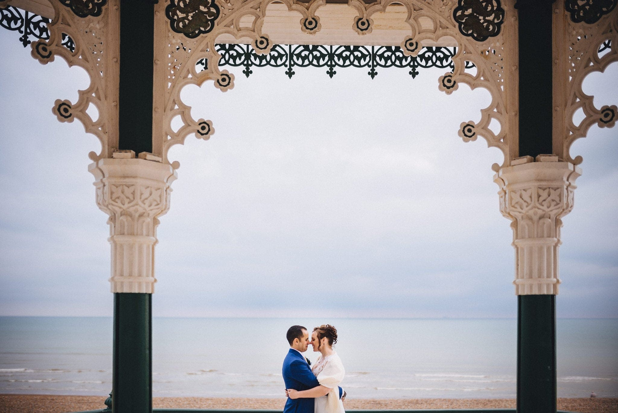 Bride and groom embrace on Brighton bandstand with sea in the background