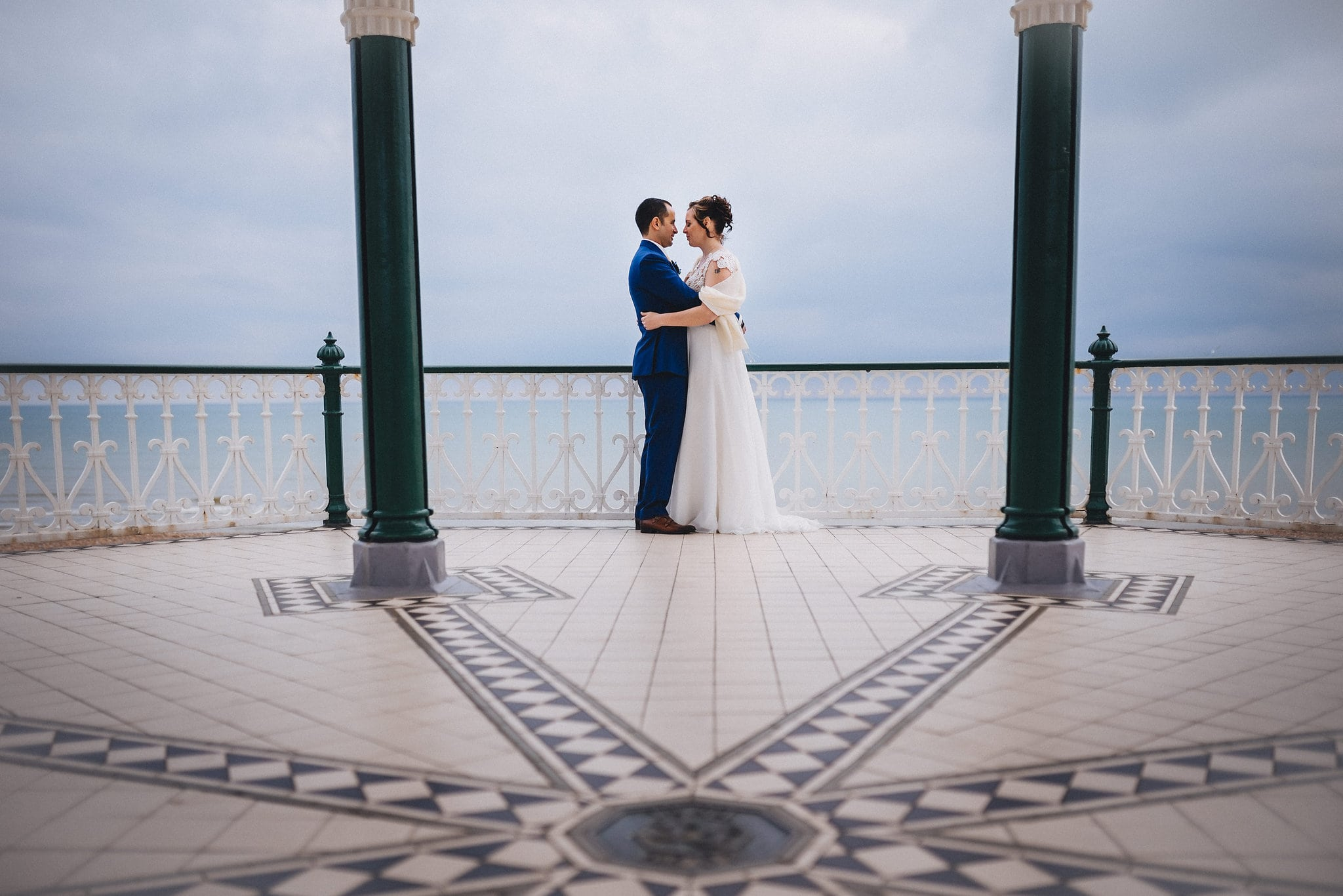 Bride and groom hug on bandstand on Brighton beach