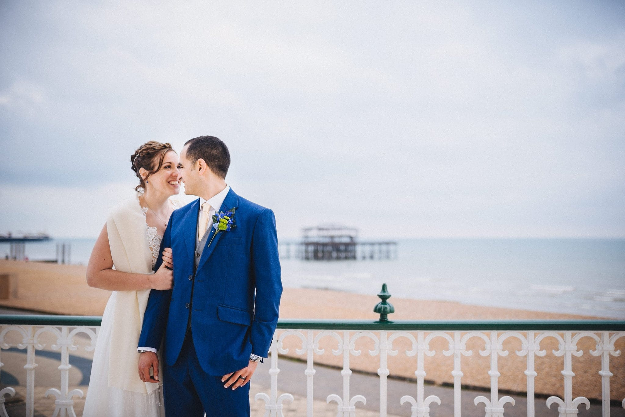Bride holds groom's arm on Brighton bandstand with beach in the background