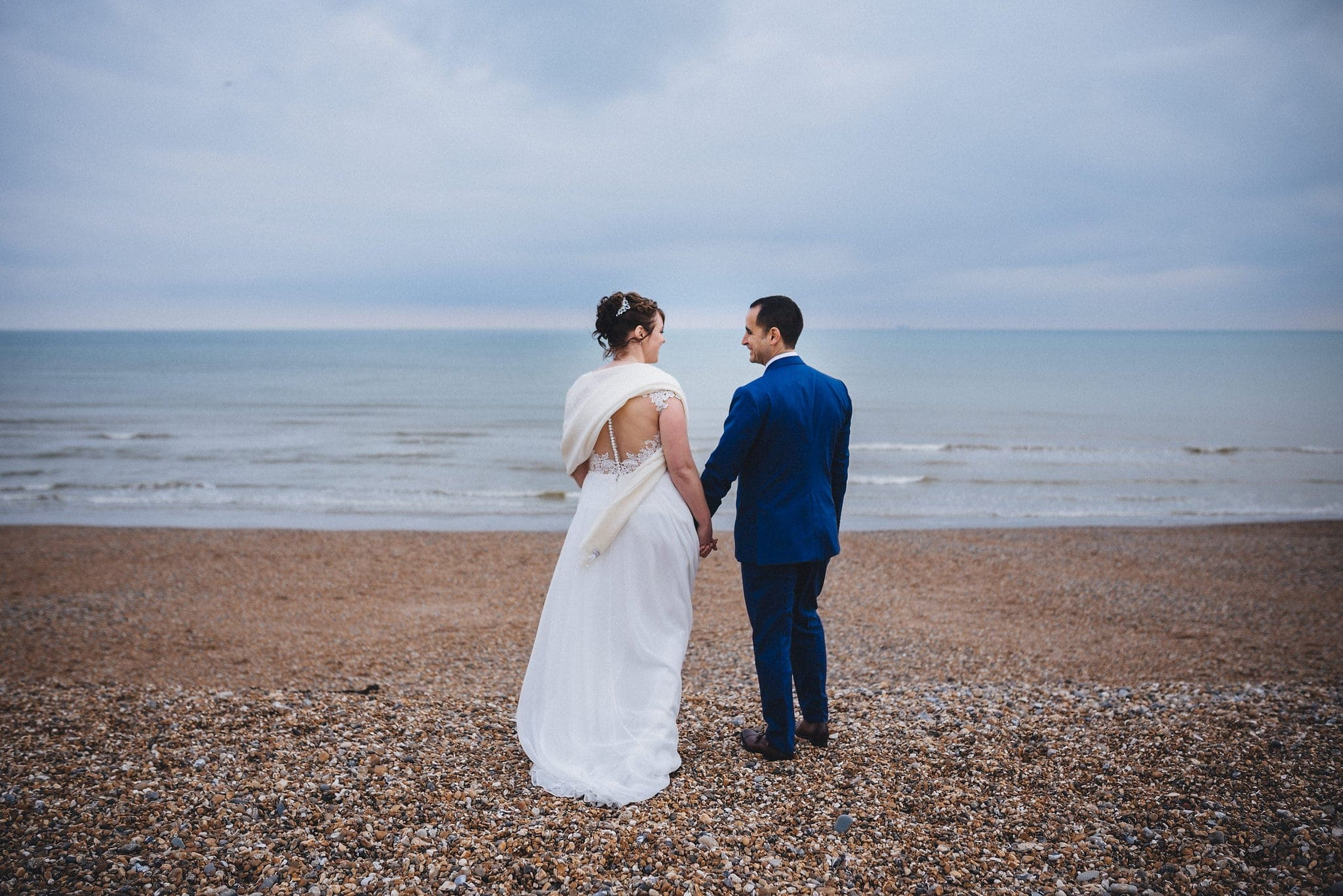 Bride and groom hold hands on deserted Brighton beach