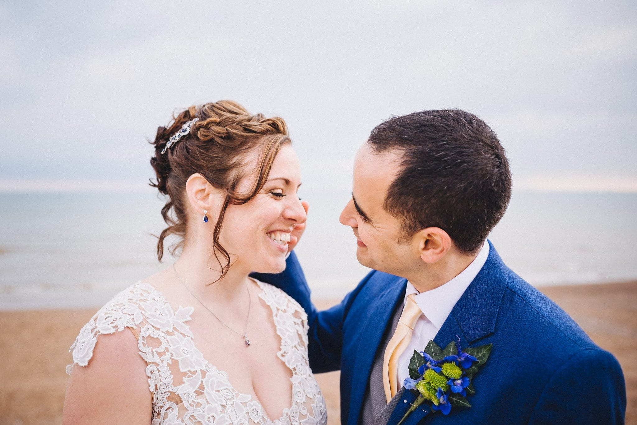 Bride and groom laugh together on Brighton beach