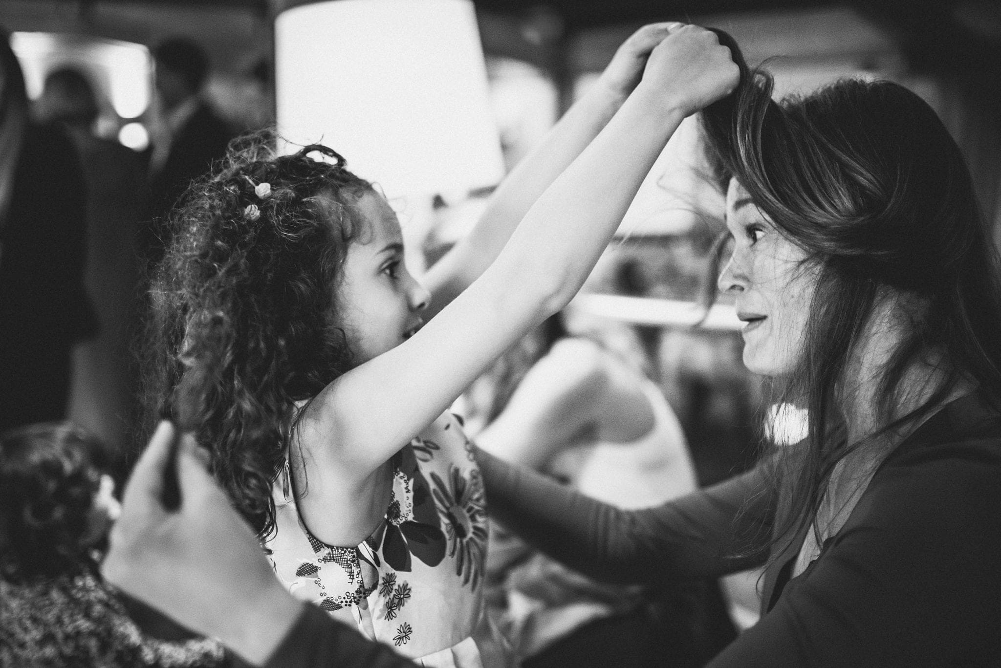 Child plays with guest's hair at wedding reception