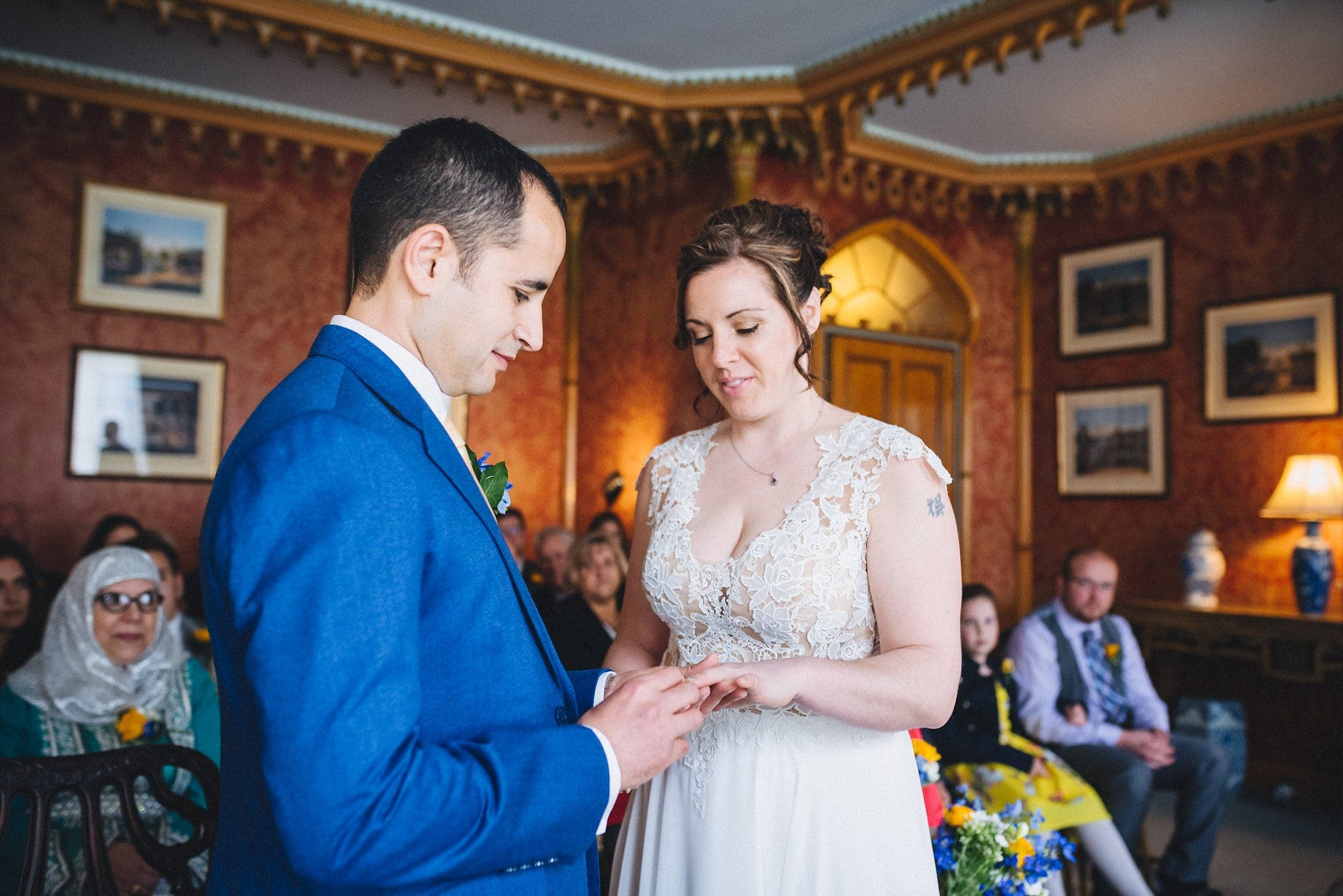 Groom places bride's ring on her finger at Brighton Royal Pavilion wedding