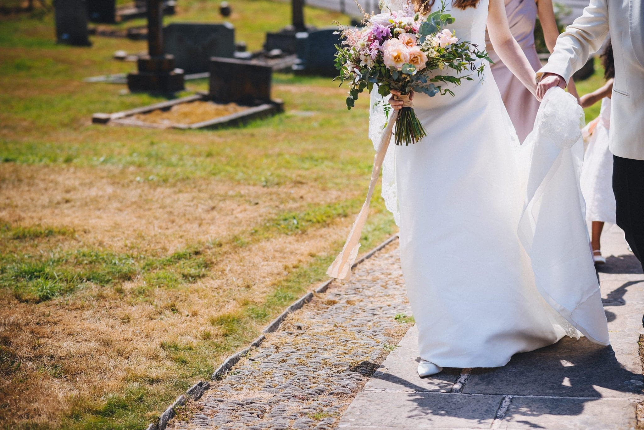Lower half of bride's dress and bouquet as she walks up path to the church