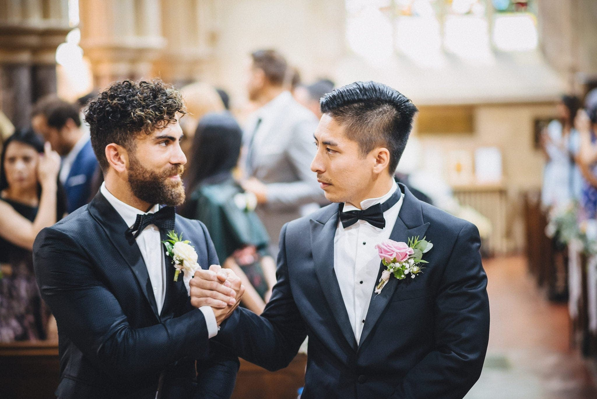 Groom at best man clasp hands while waiting for bride at church