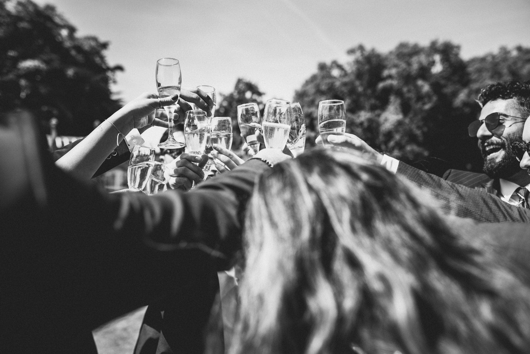 Black and white shot of large toast with many champagne glasses clinking together