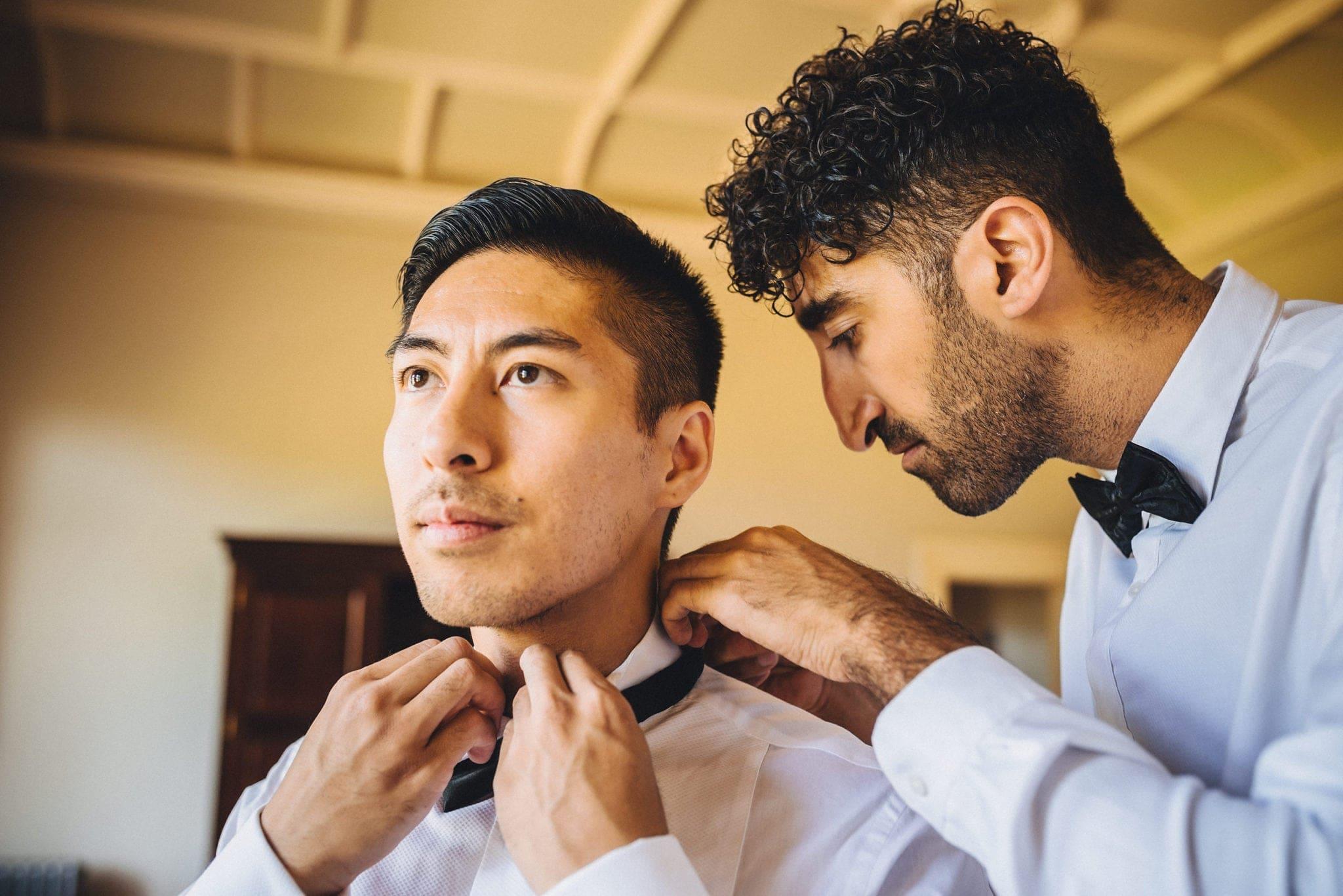 Groomsman fastens groom's bowtie