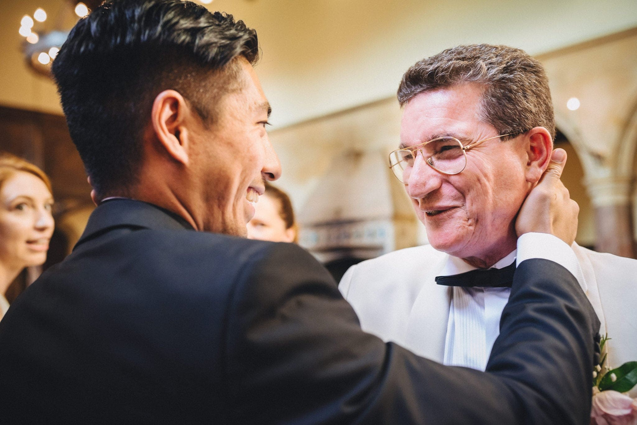 Groom and father of the bride share a tender moment