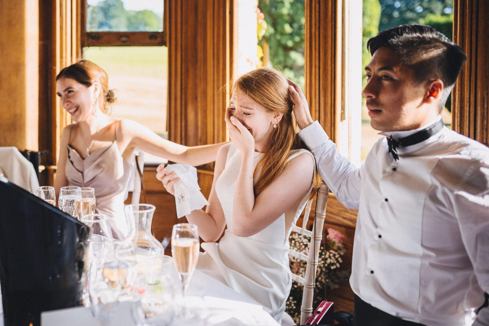 Groom strokes bride's hair as she cries during wedding speeches