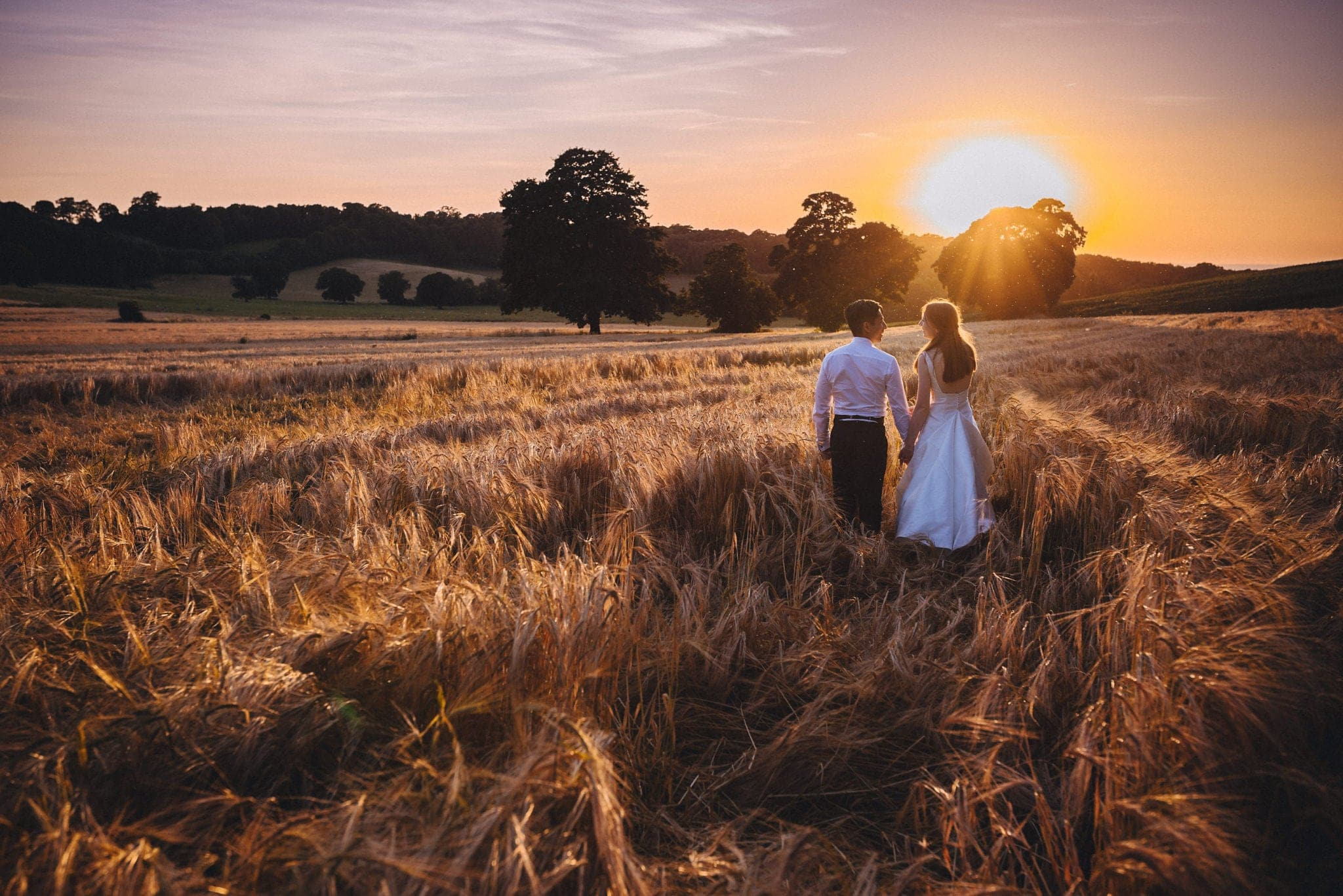 Bride and groom in wheatfield at sunset