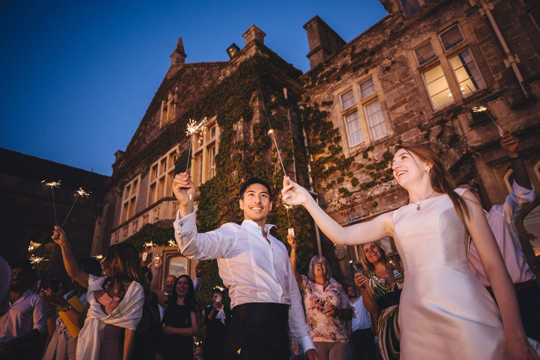 Bride, groom and guests hold sparklers outside manor house at their glamorous St Audries Park wedding