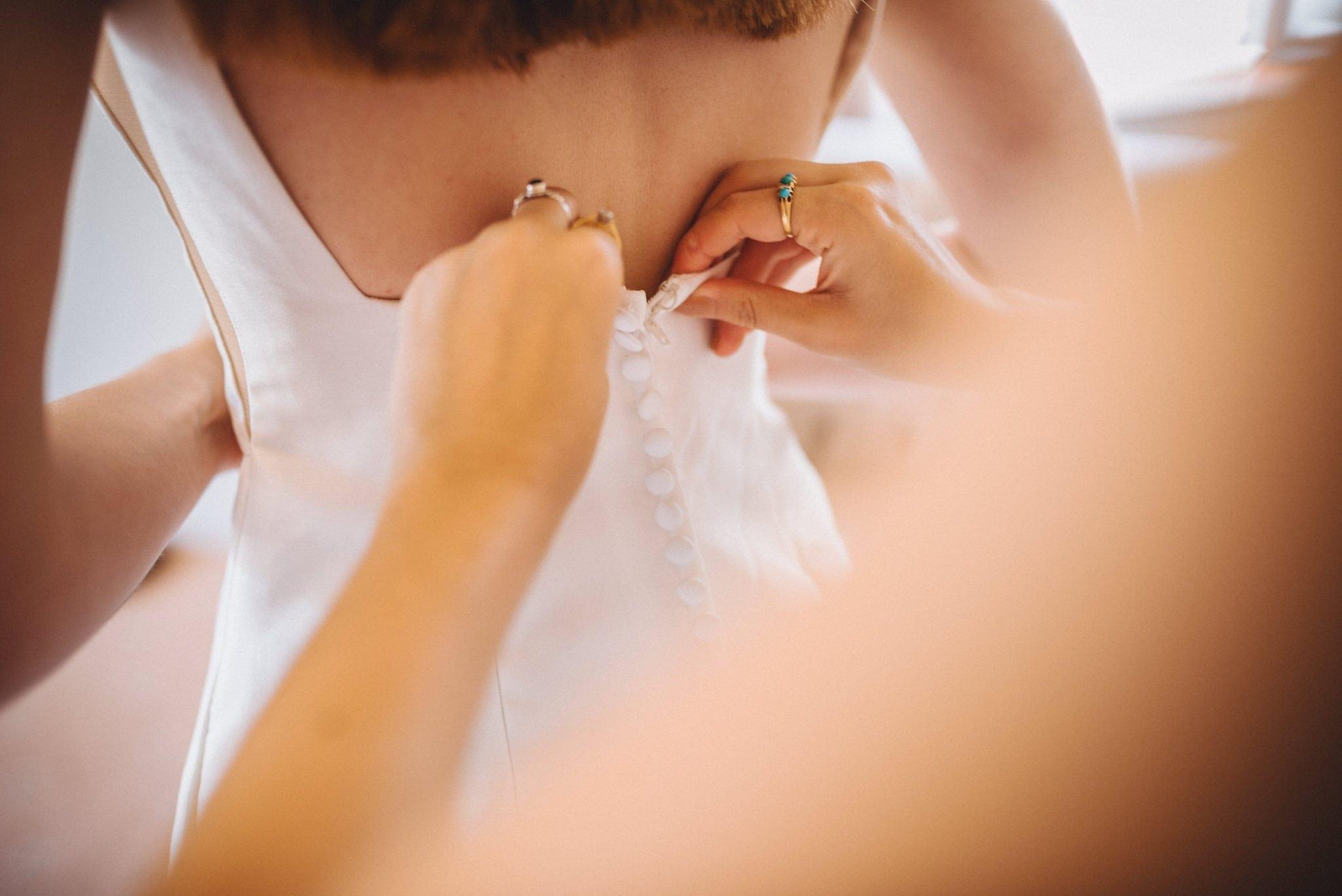 Close up of the bride's dress being done up