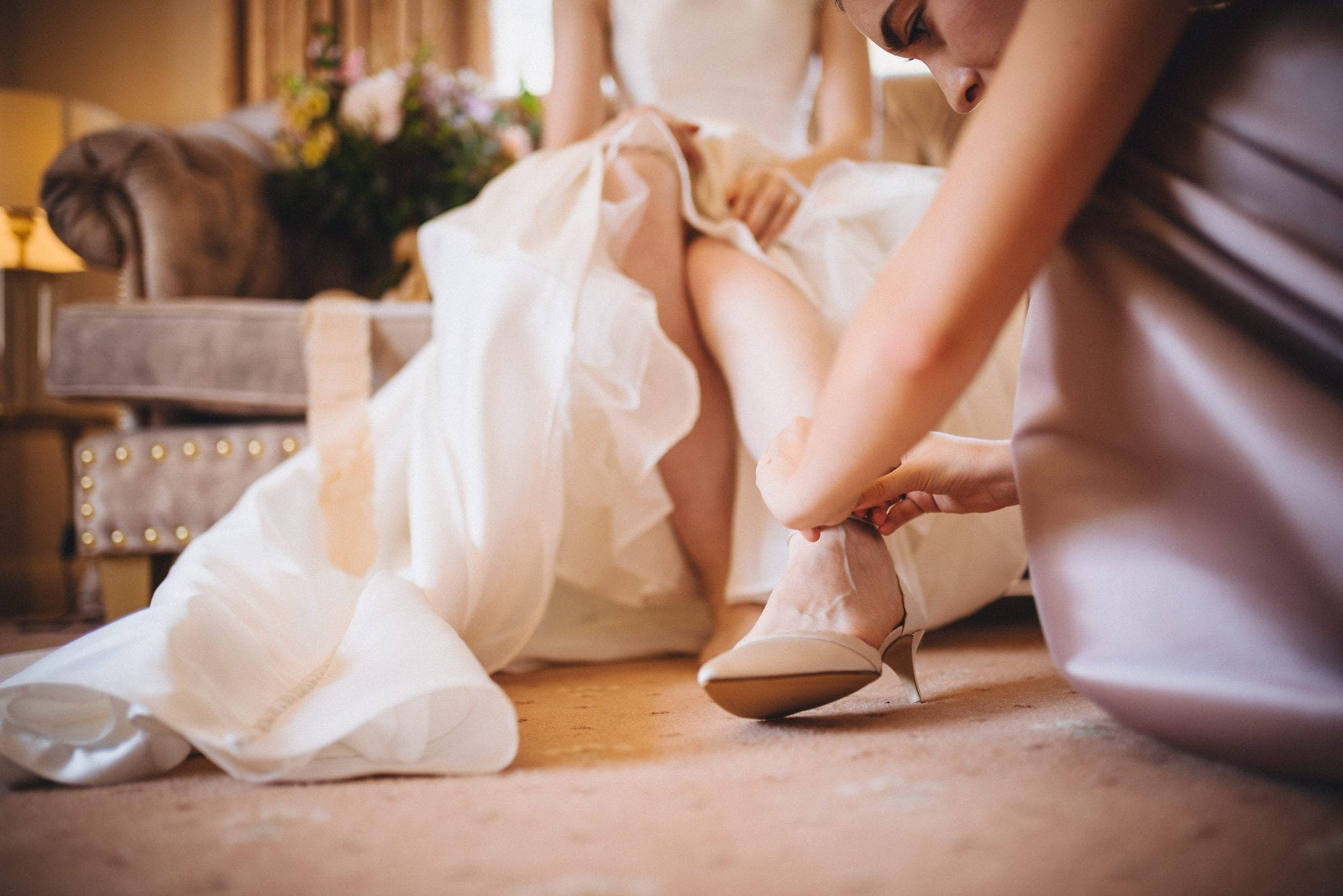 Bridesmaid fastens bride's shoe