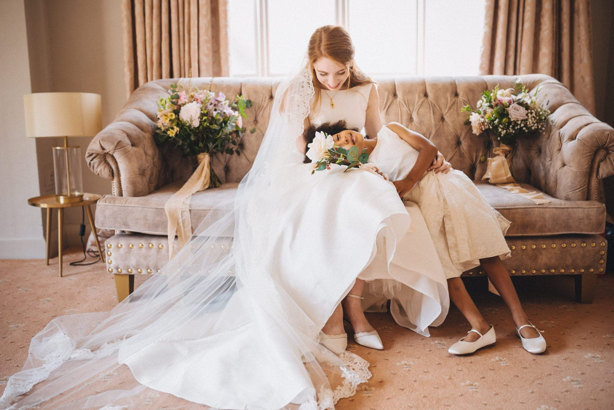 Flower girl lies with her head in bride's lap on velvet sofa
