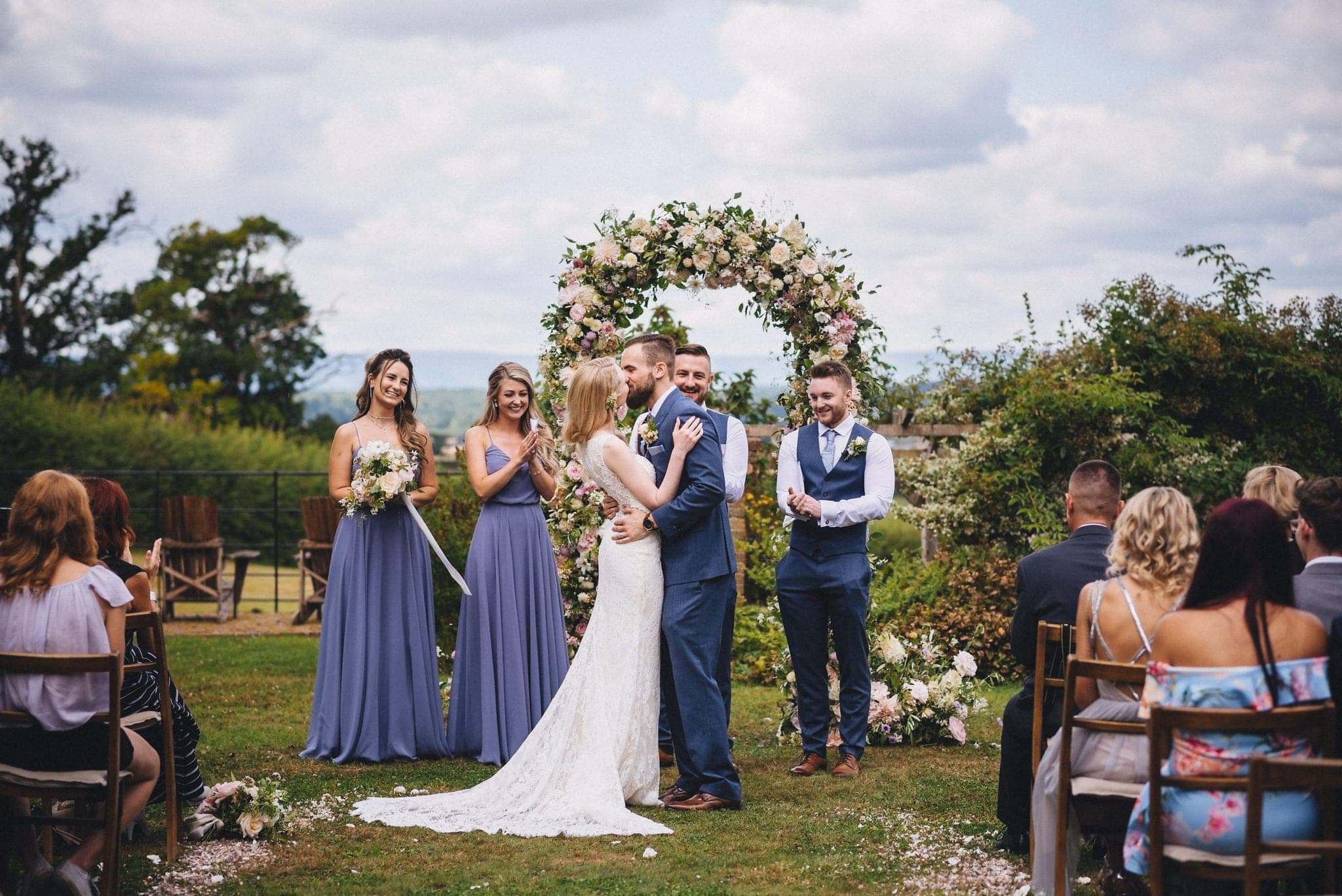 Bride and groom kiss in front of flower arch