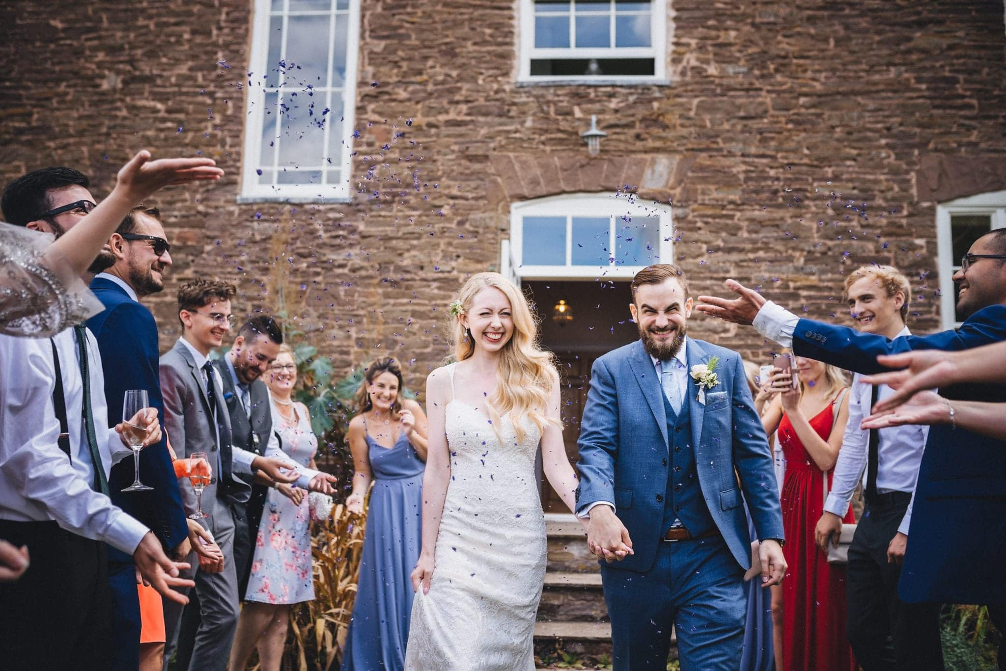 Bride and groom get covered in purple confetti petals at their Dewsall Court wedding
