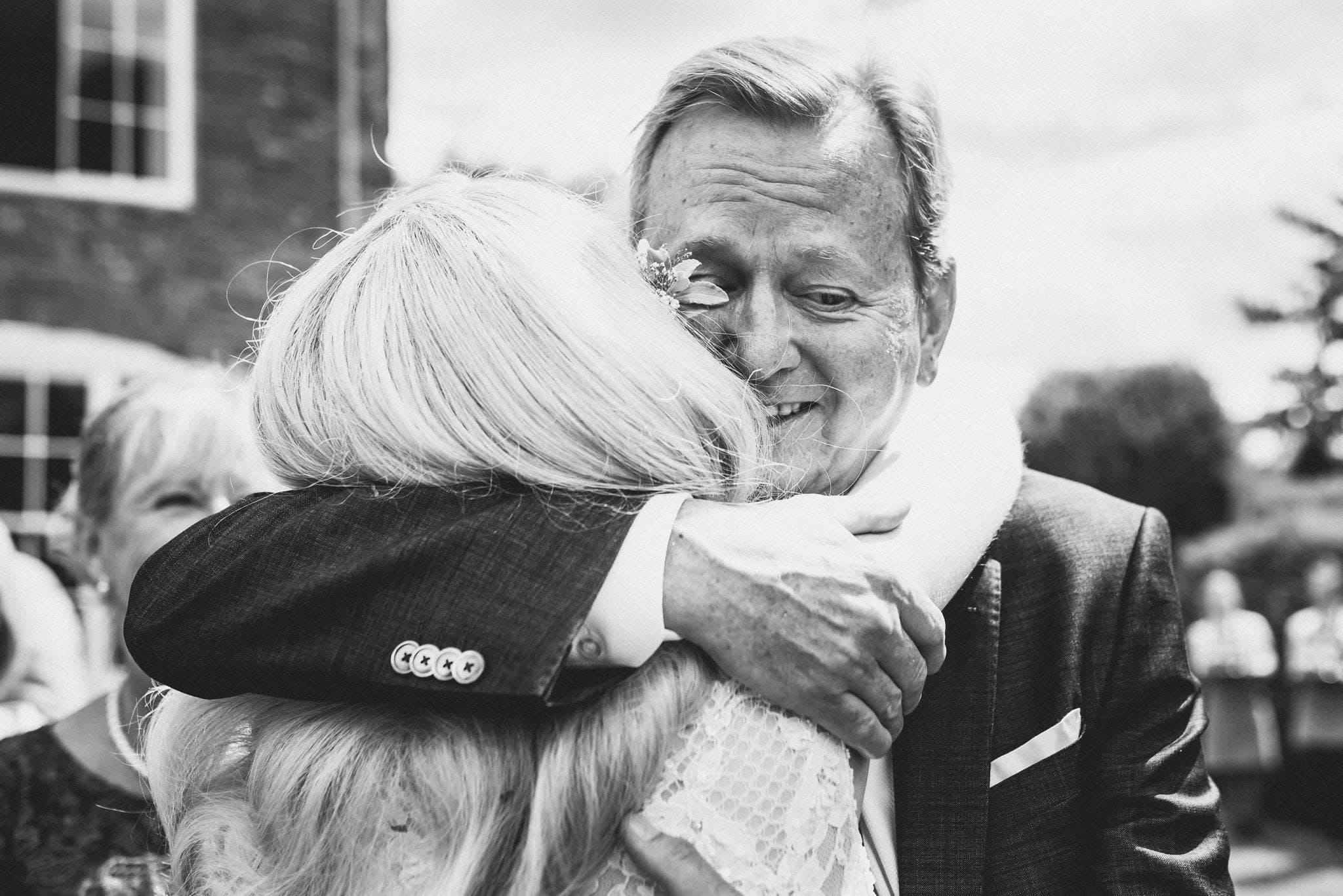 Black and white shot of bride hugging her dad at Dewsall Court wedding