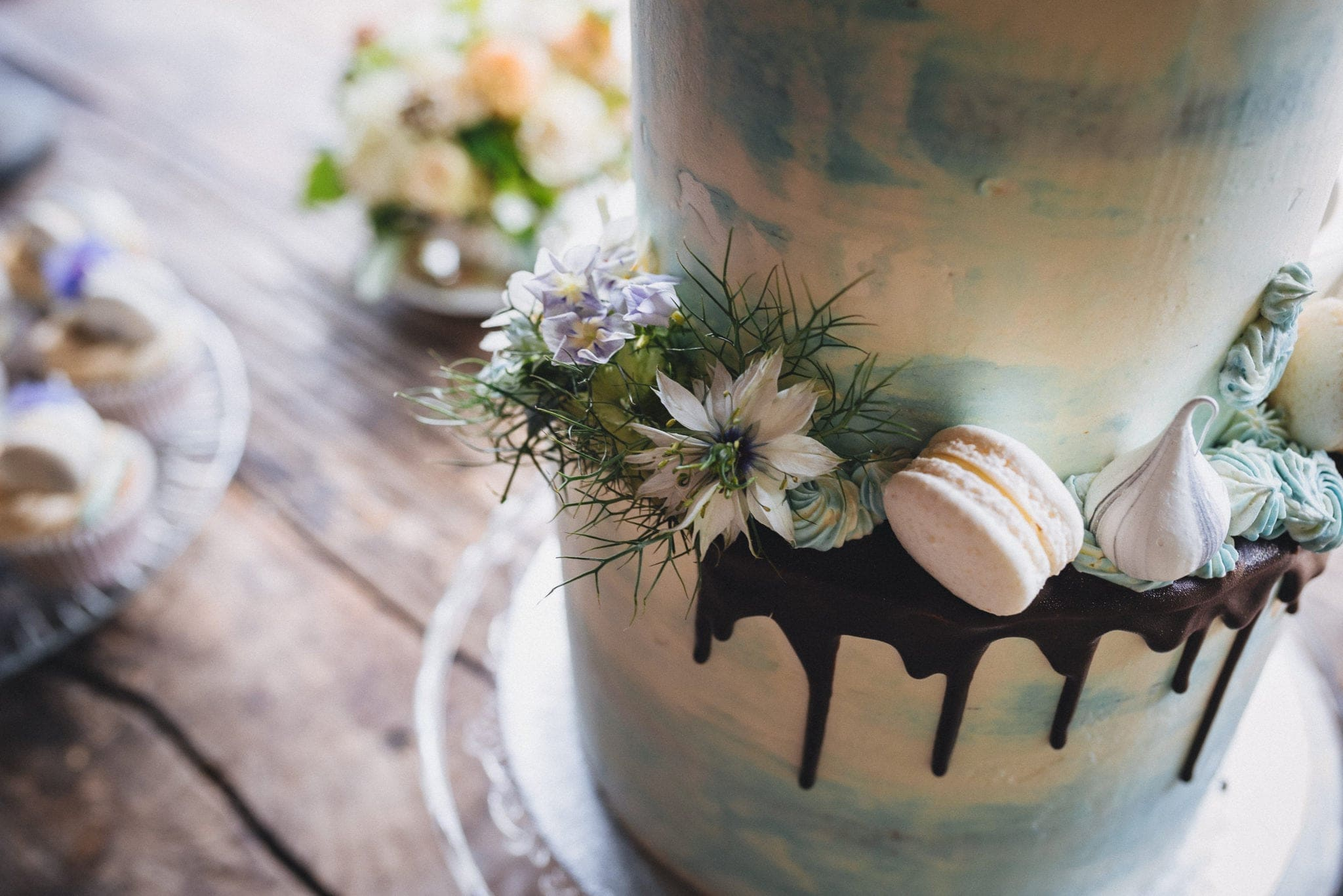 Blue and cream cake with chocolate drip, flowers and macarons