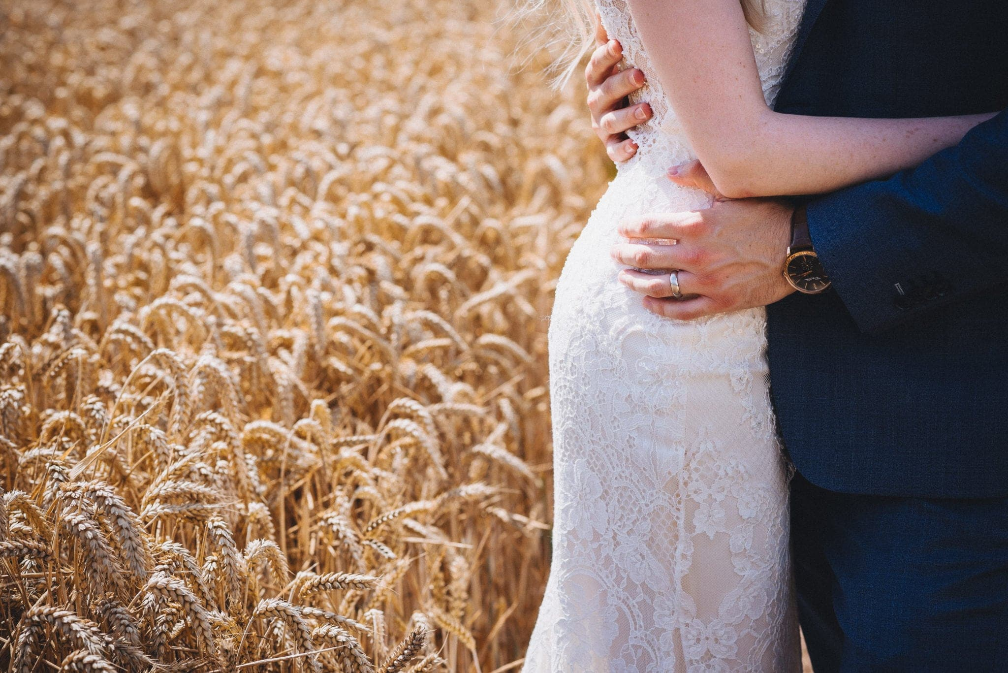 Bride and groom with their arms around each other's waists standing in a summer corn field