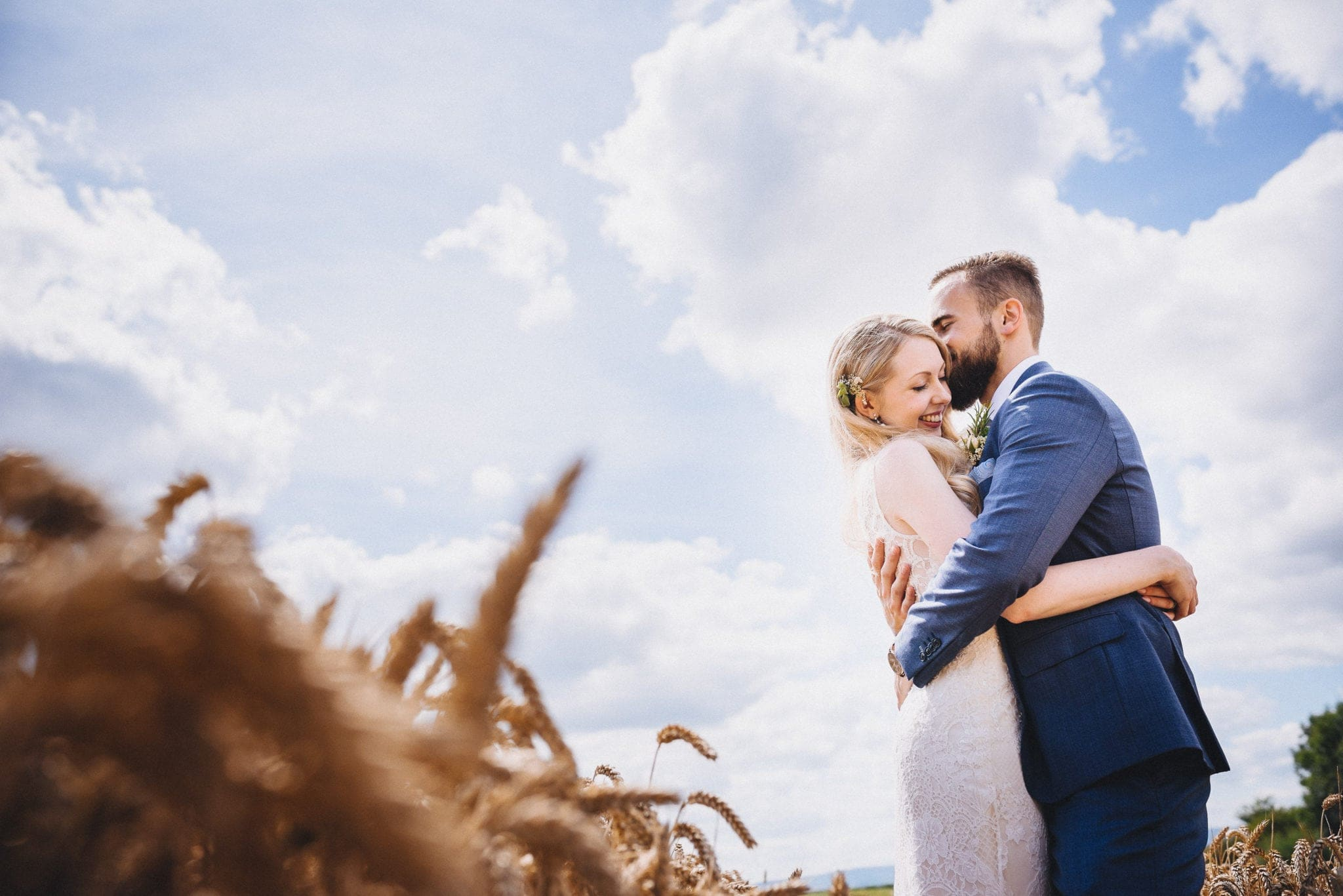 Bride and Groom embrace in a sunny corn field