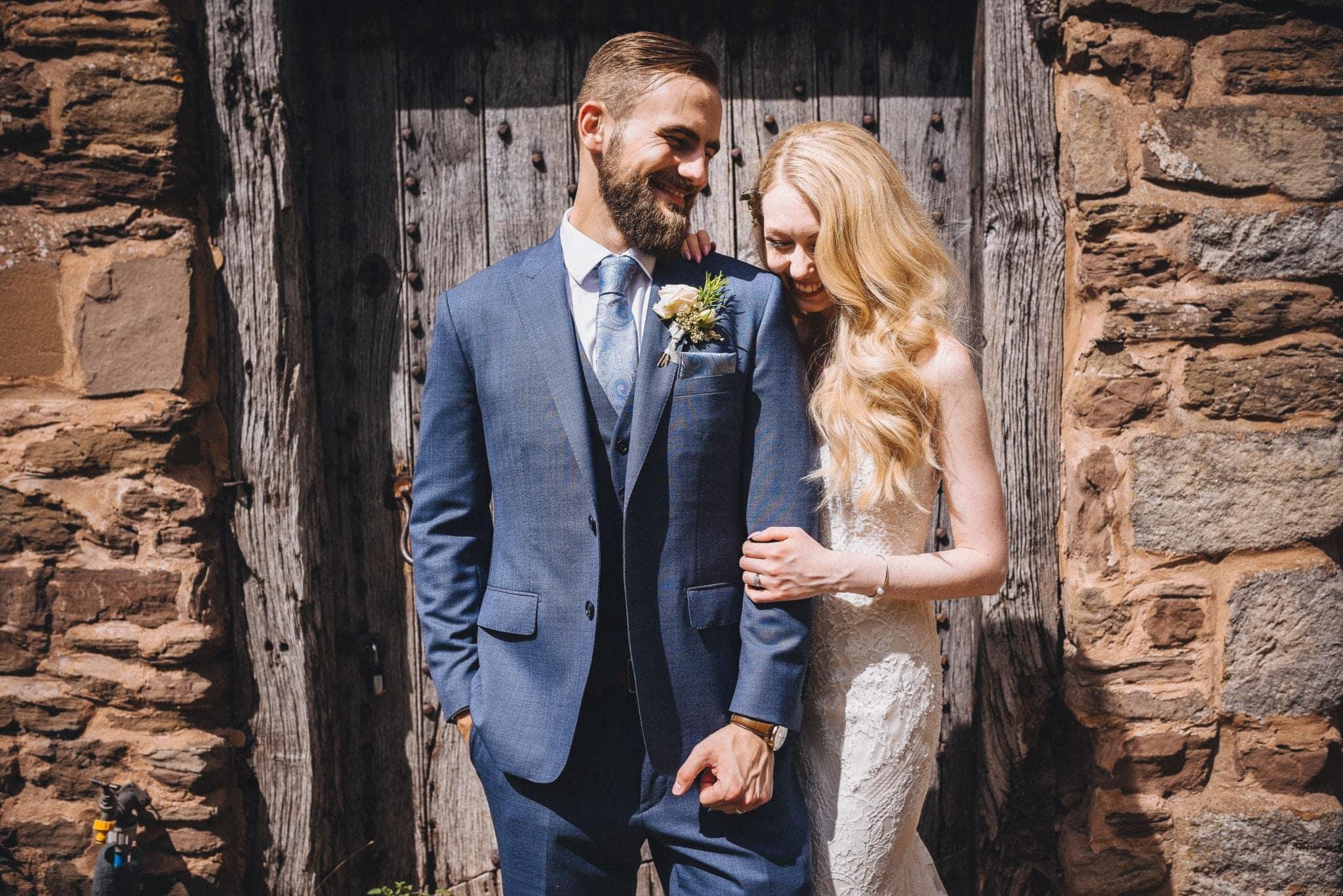 Bride and groom pose in front of wooden door