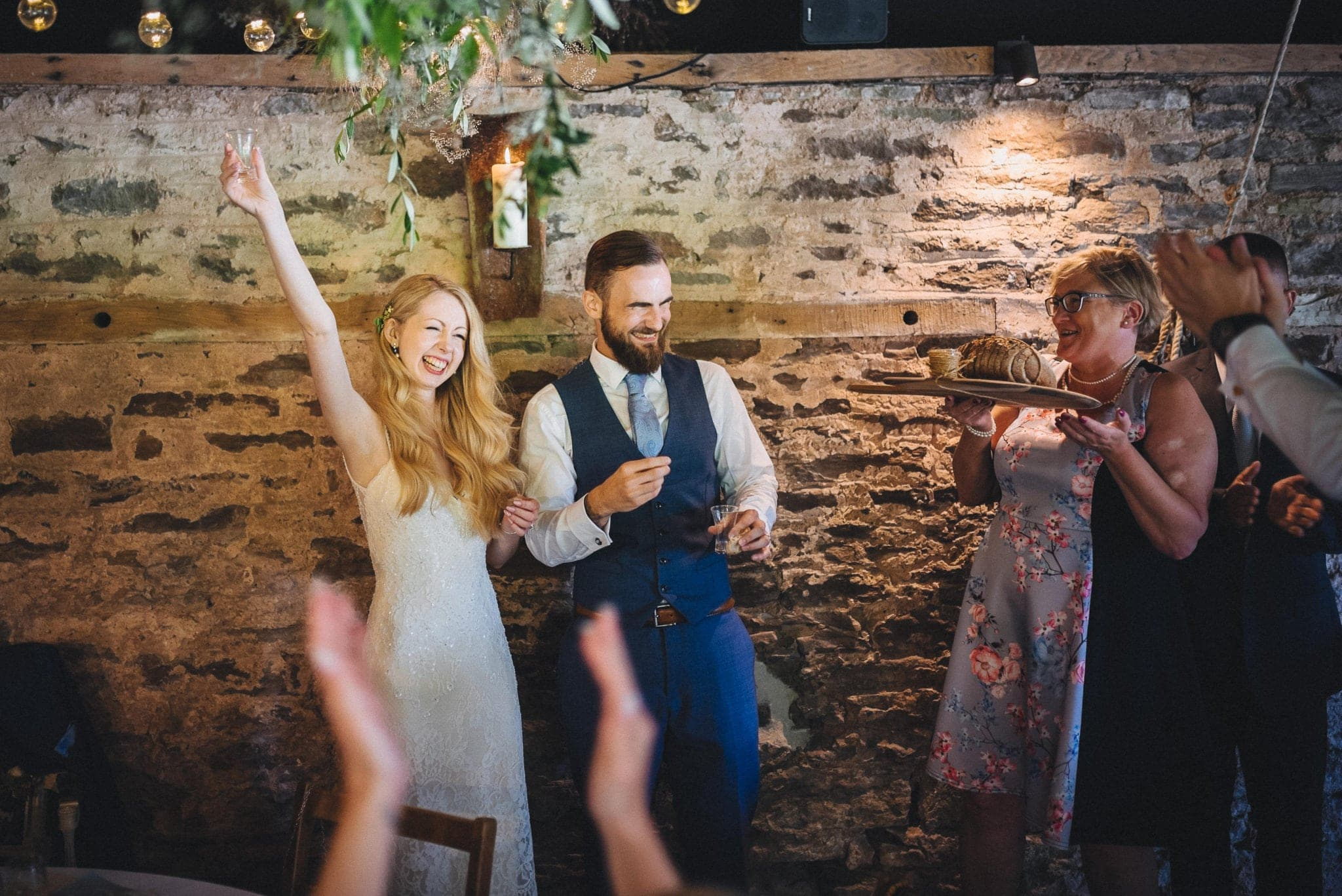 Bride laughs and punches the air after doing a shot with groom during speeches