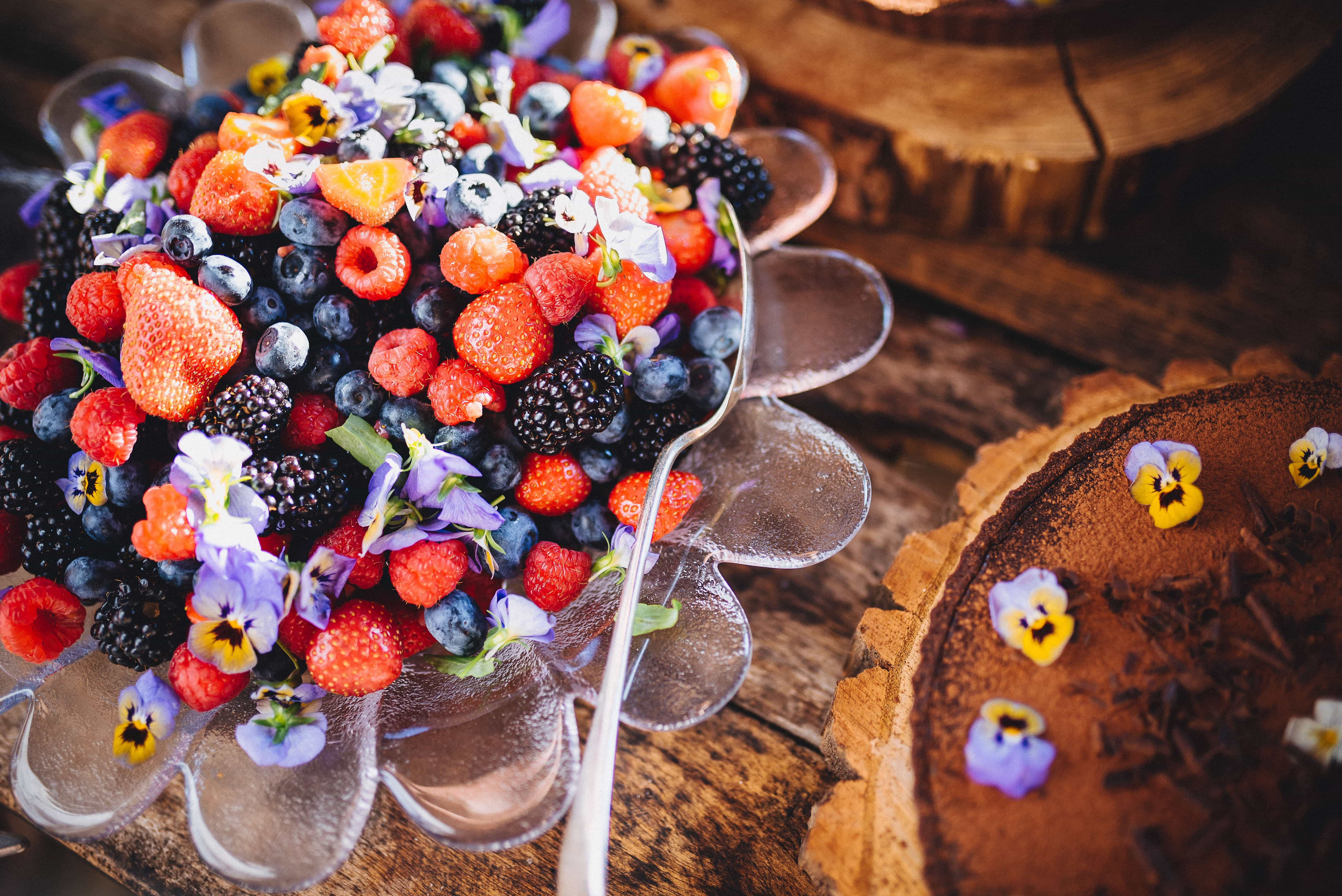 Cakes with bright berries and flowers at Dewsall Court wedding