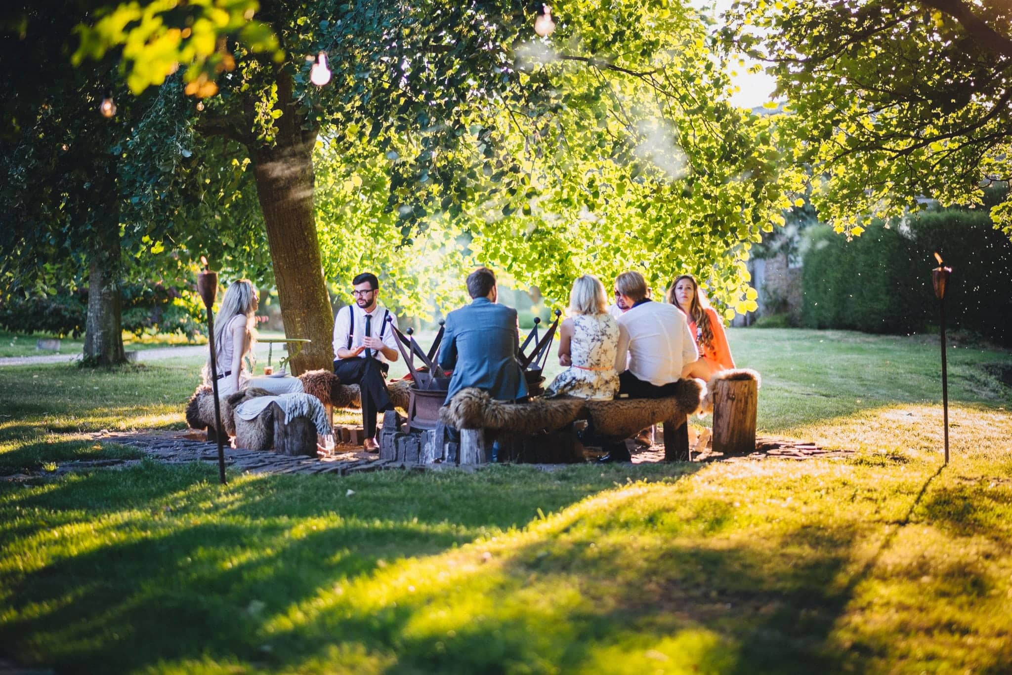 Guests sit around fire pit at Dewsall Court in the sunshine