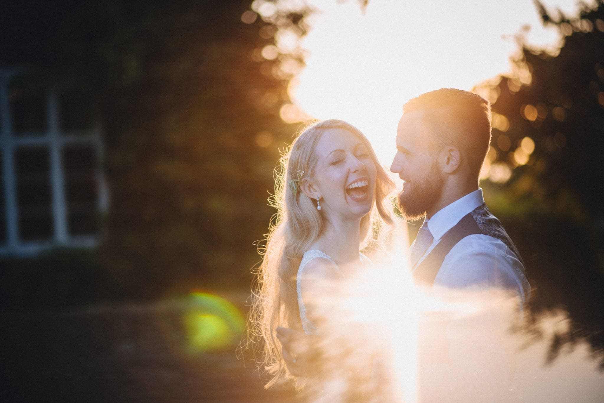 Bride and groom laughing at sunset at Dewsall Court
