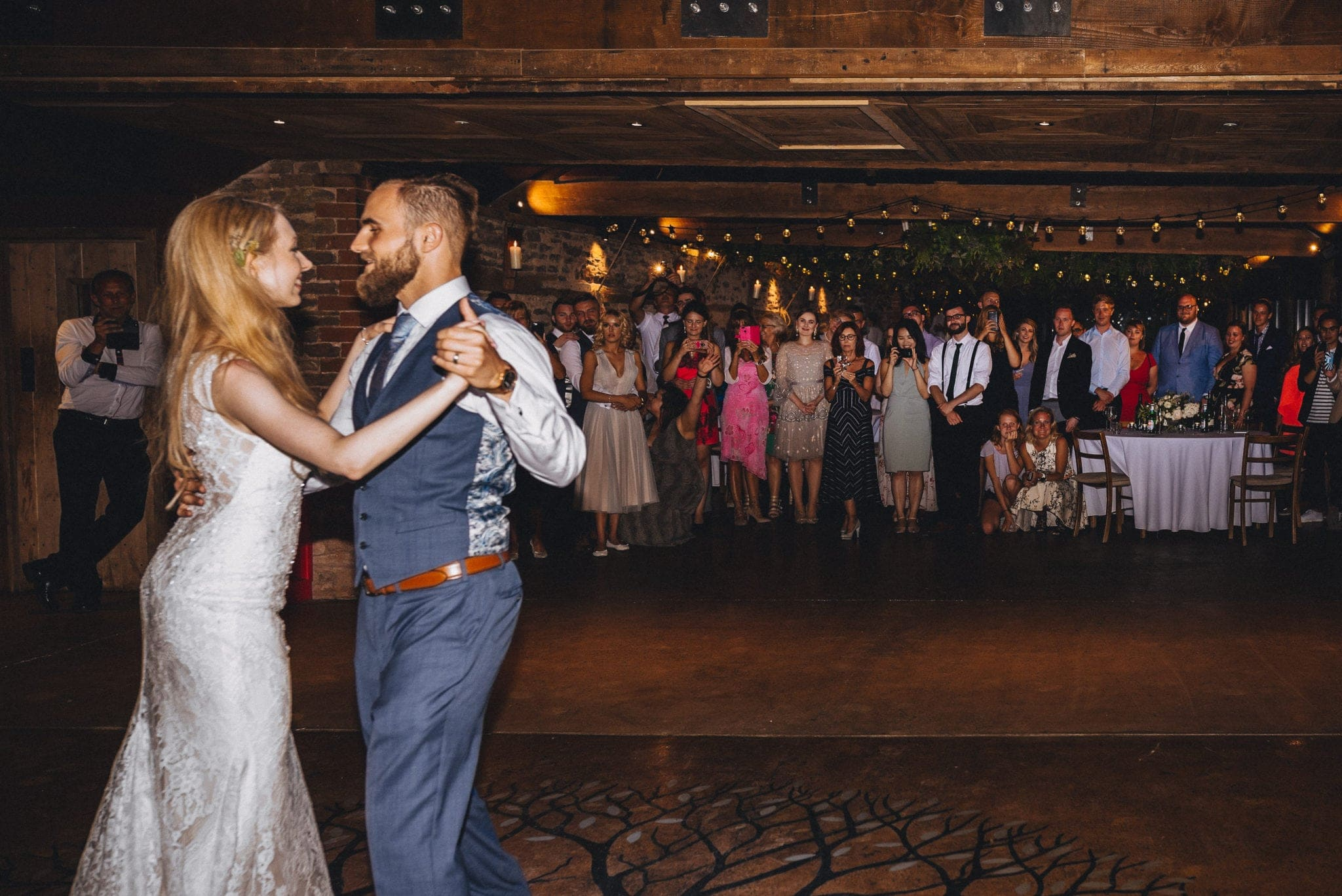 Bride and groom dance together as guests look on
