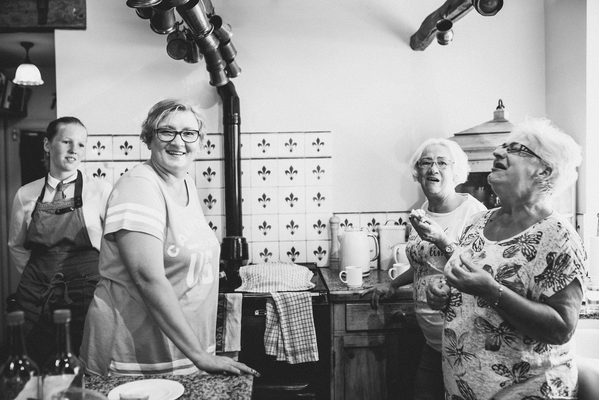 Black and white shot of mum and grandmothers laughing in the kitchen at Dewsall Court