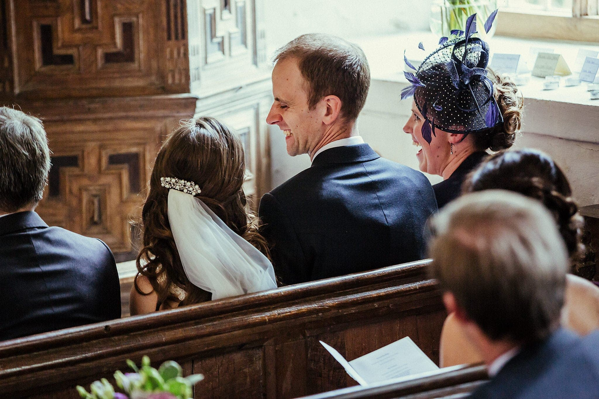 Bride and groom laughing in a pew in church during ceremony