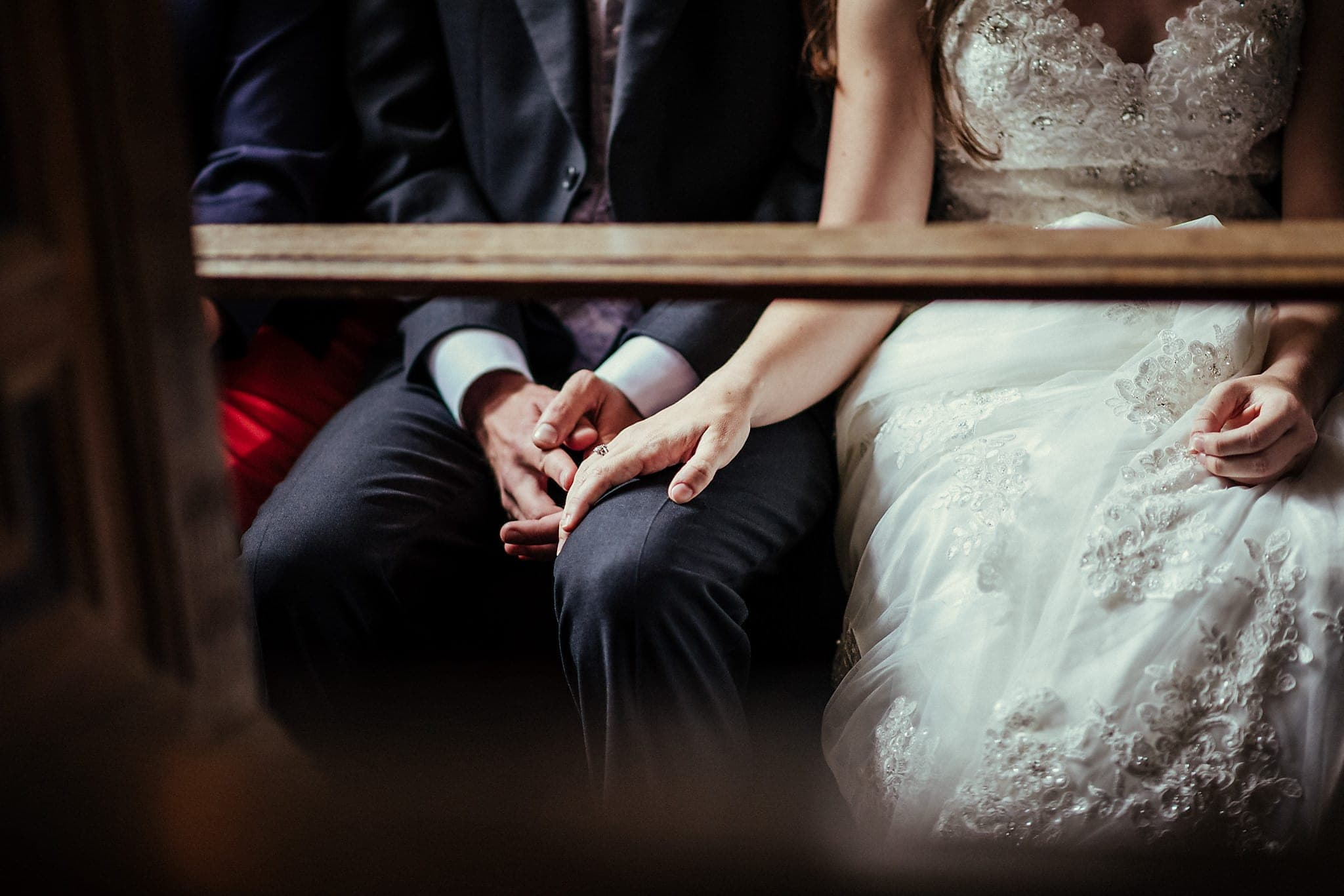 Bride holding groom's hand under the pews at Dorney Court Church