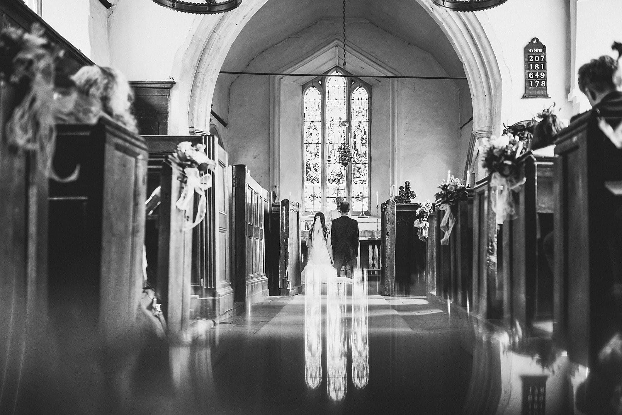 Bride and Groom kneeling at Dorney Court Church