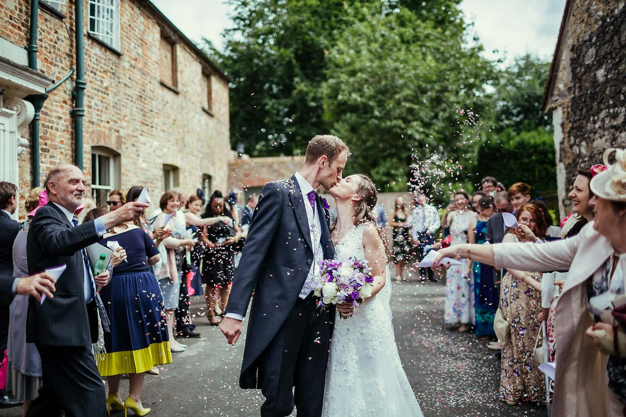 Bride and groom kiss amid purple confetti petals at Dorney Court